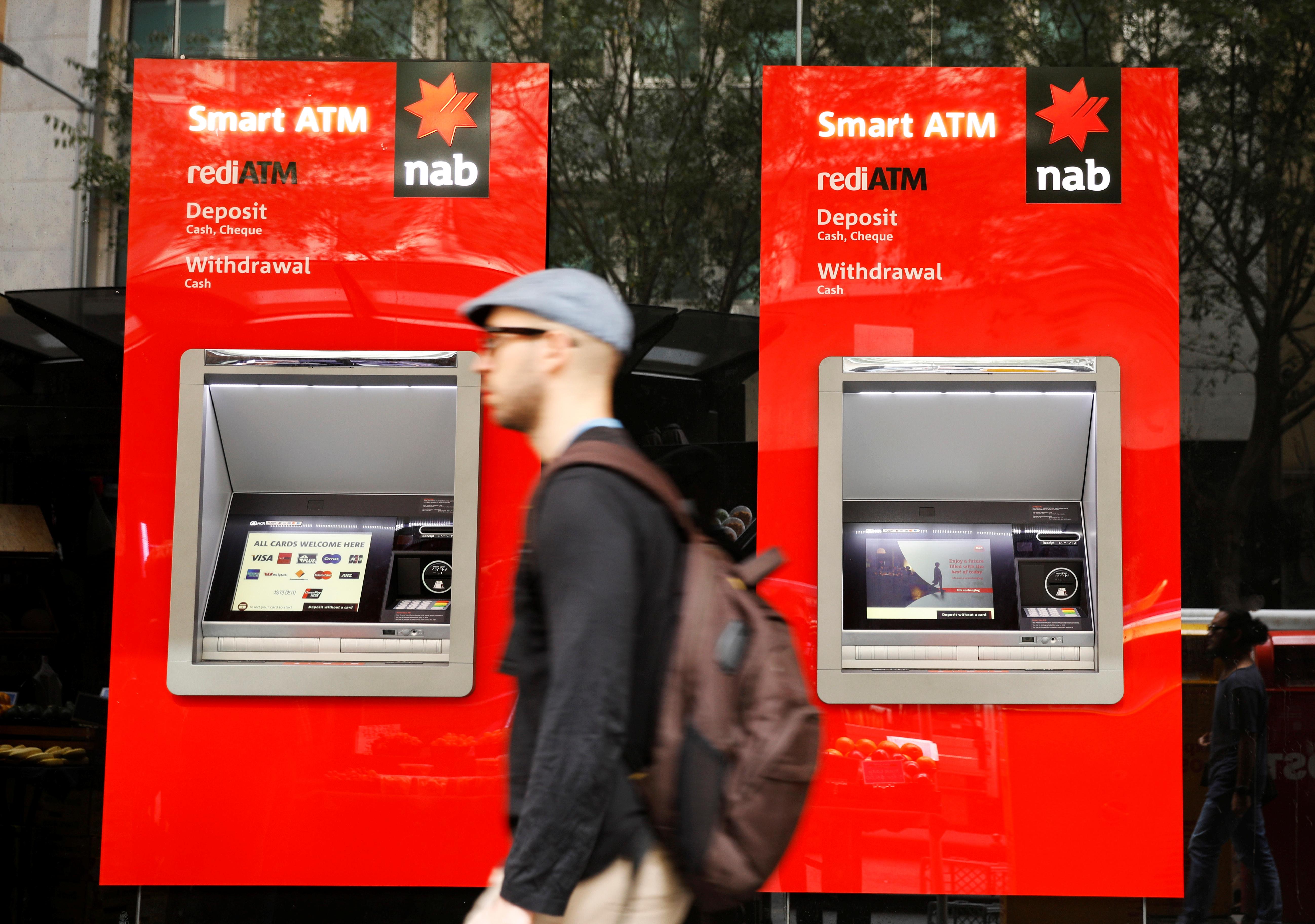 A man walks past ATM machines at a National Australia Bank branch in Sydney, Australia April 20, 2018. REUTERS/Edgar Su