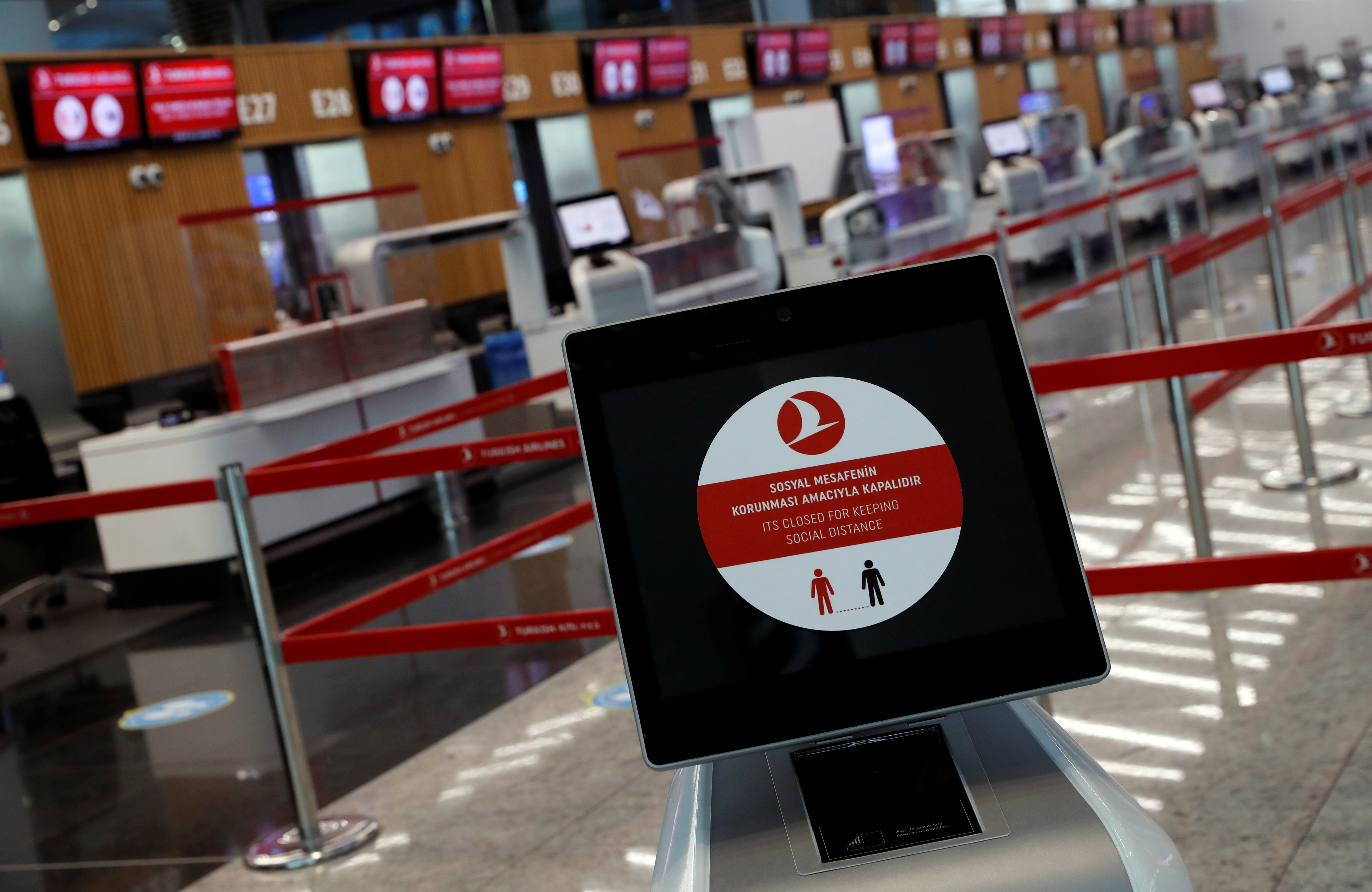 A social distancing sign is seen before the Turkish Airlines check-in counters at the international departure terminal of the Istanbul Airport amid the coronavirus disease (COVID-19) outbreak, in Istanbul, Turkey June 19, 2020. REUTERS/Murad Sezer