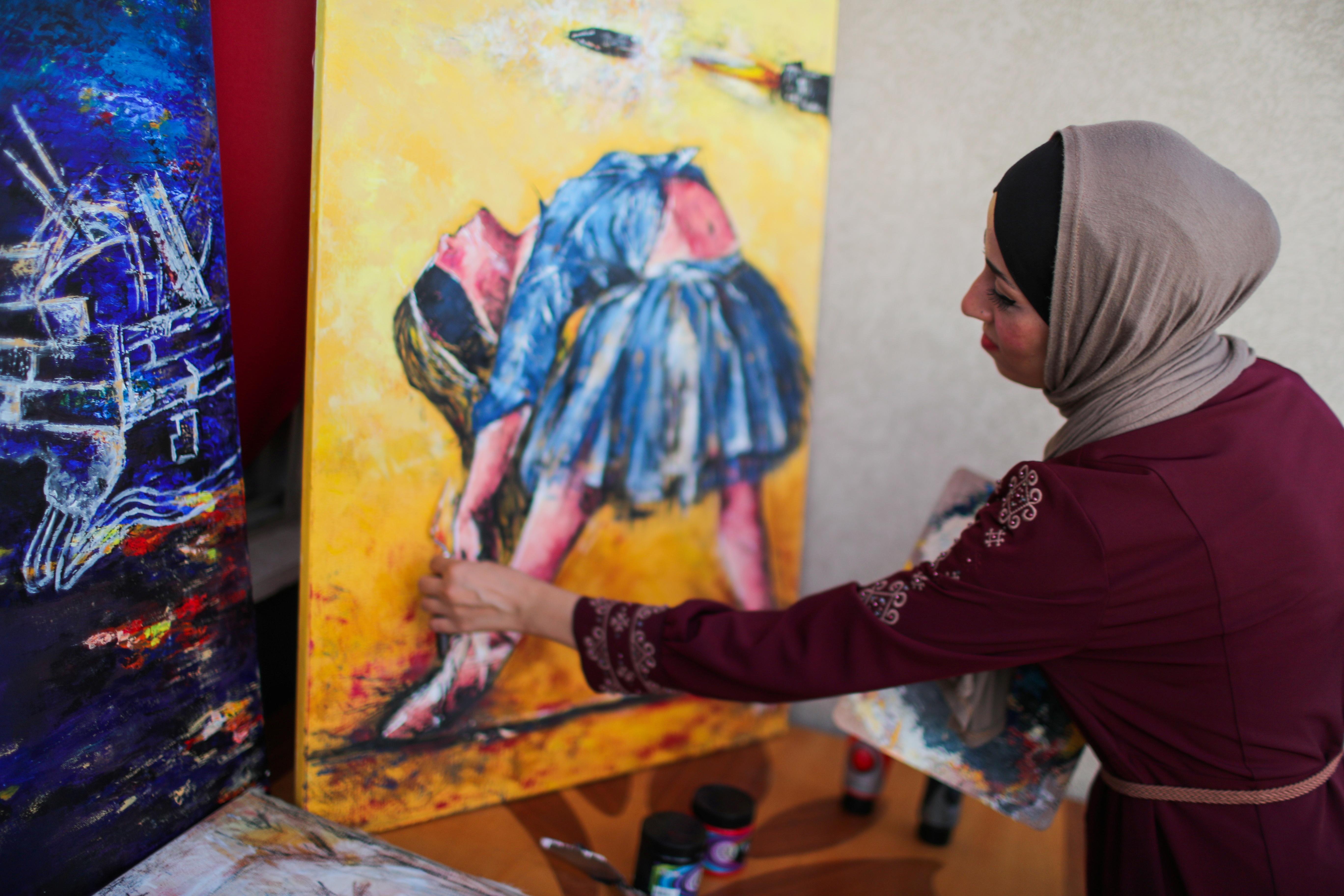 A Palestinian artist, Abeer Jibril, works on ballet paintings at her home in Gaza City, September 8, 2021. Picture taken September 8, 2021. REUTERS/Mohammed Salem