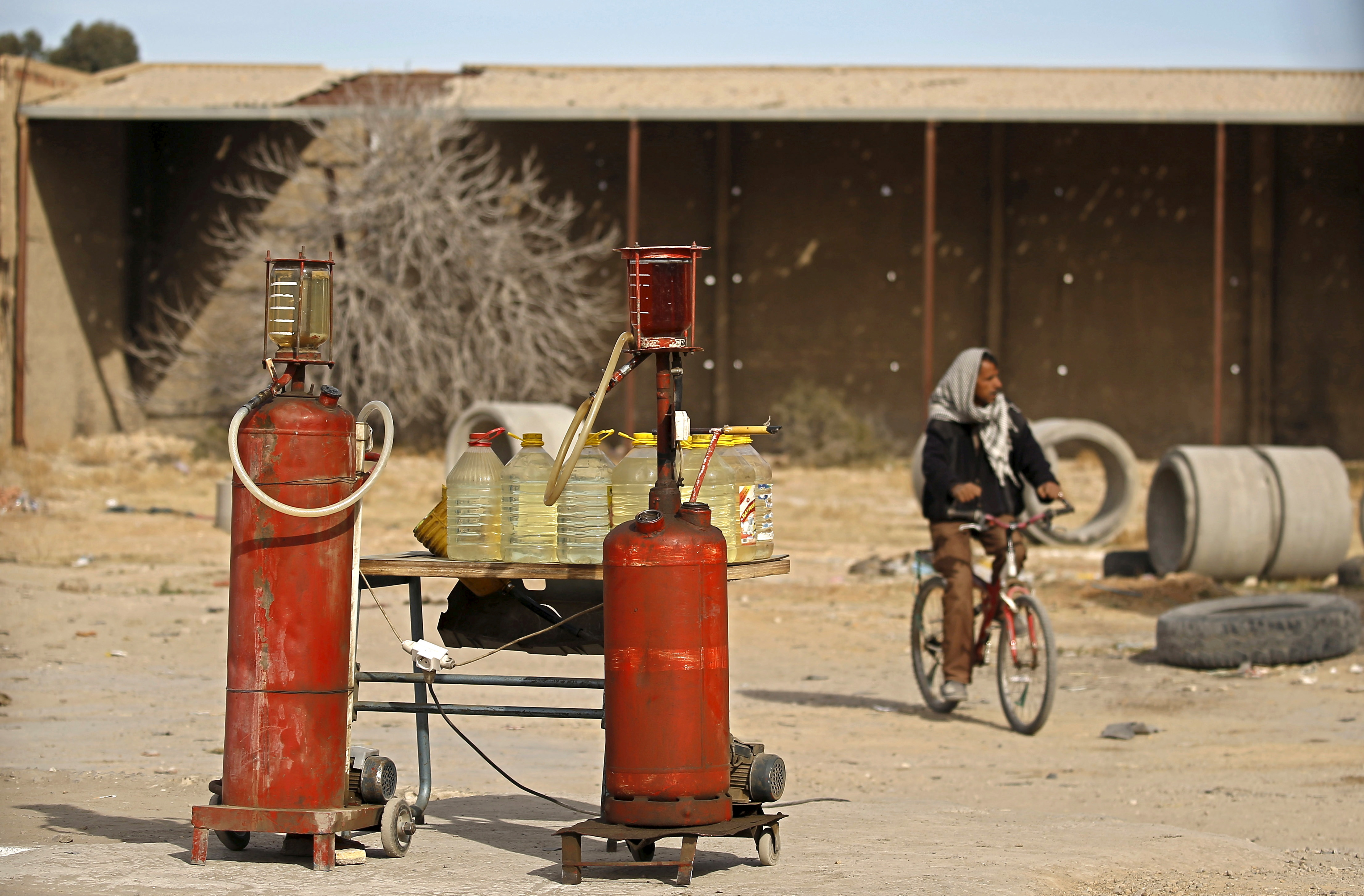 A man rides a bicycle as he passes tanks of gasoline in Kasserine, Tunisia January 30, 2016. REUTERS/Zohra Bensemra/File Photo