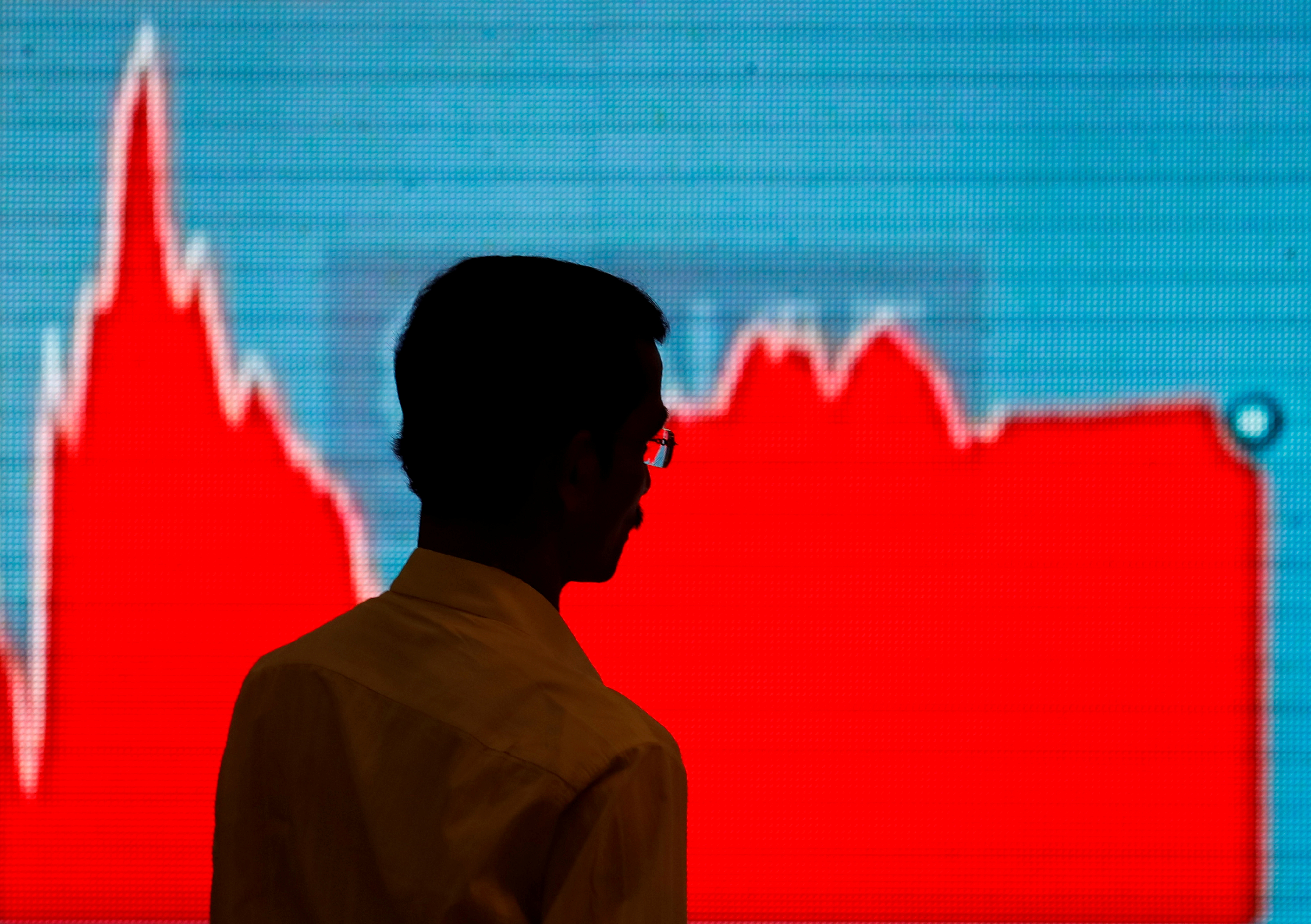 A man walks past a screen displaying news of markets update inside the Bombay Stock Exchange (BSE) building in Mumbai, India, February 6, 2018. REUTERS/Danish Siddiqui/Files