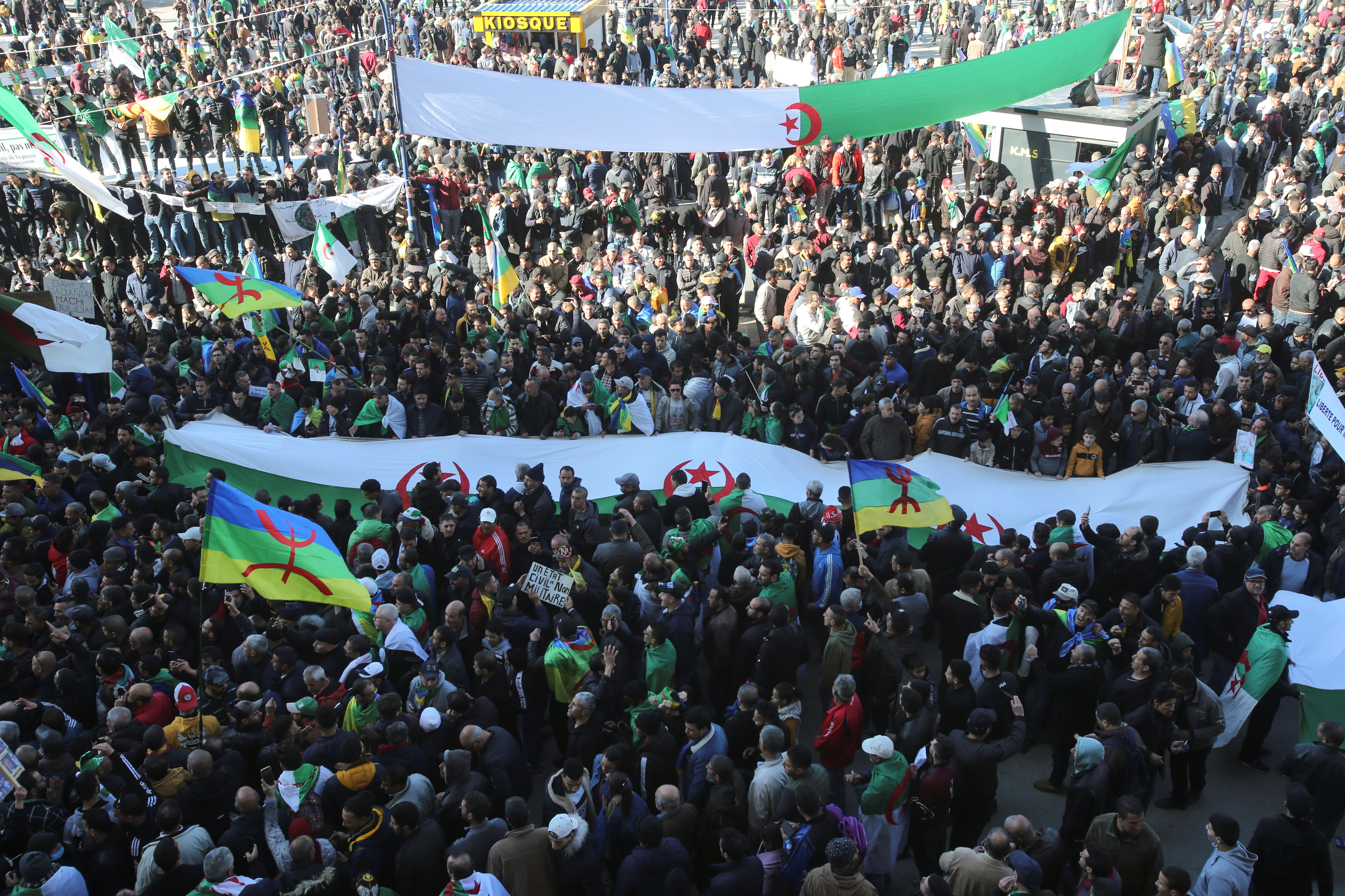 Demonstrators carry flags as they gather in the town of Kherrata, marking two years since the start of a mass protest movement there demanding political change, Algeria February 16, 2021. REUTERS/Ramzi Boudina