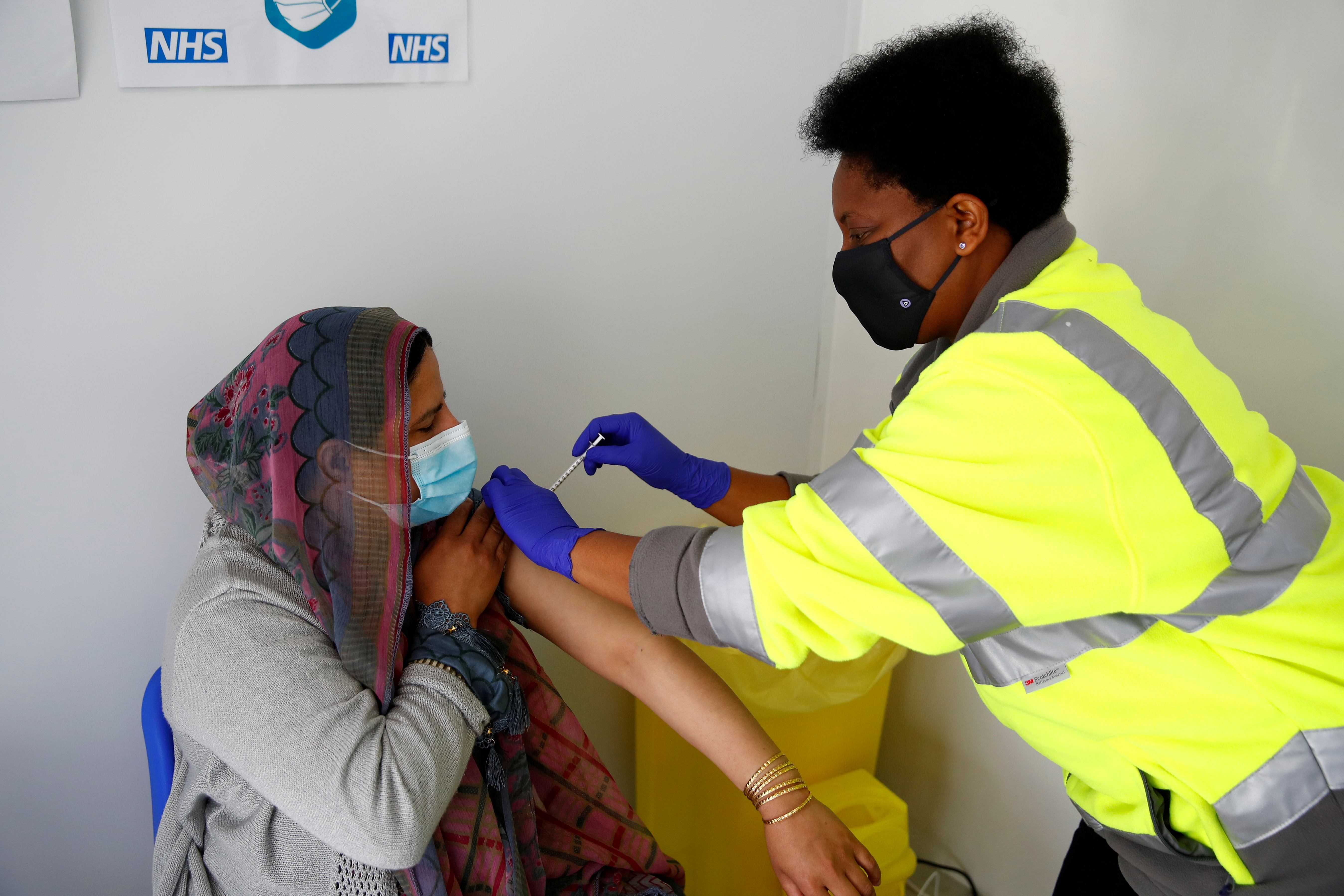 Nasreen Akhtar, 35, receives a dose of Pfizer vaccine against COVID-19 at a vaccination centre in Pharmacy 4 U, amid the outbreak of the coronavirus disease (COVID-19), in Blackburn, Britain, May 19, 2021. REUTERS/Jason Cairnduff/File Photo