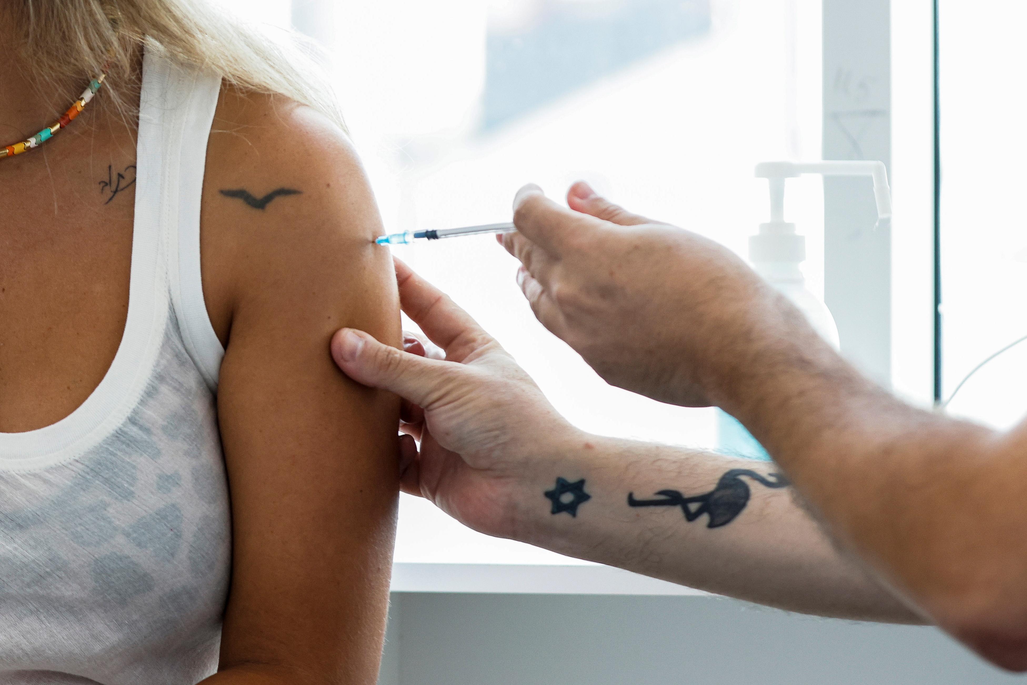 An Israeli woman receives a third shot of coronavirus disease (COVID-19) vaccine in Tel Aviv, Israel August 30, 2021. REUTERS/Amir Cohen