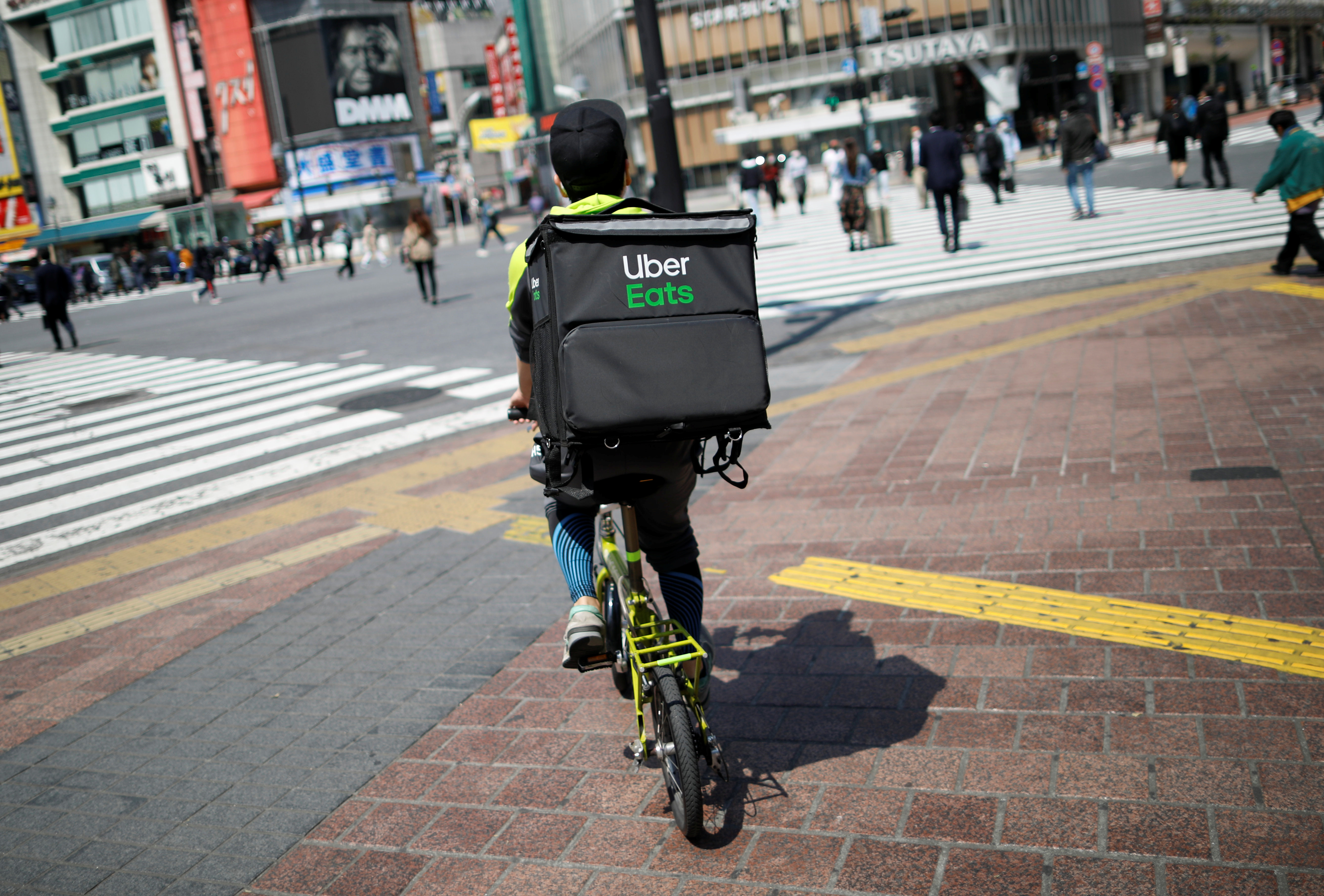 An Uber Eats delivery person rides a bicycle during an outbreak of the coronavirus disease (COVID-19), at Shibuya shopping and amusement district in Tokyo, Japan April 8, 2020.  REUTERS/Issei Kato/Files