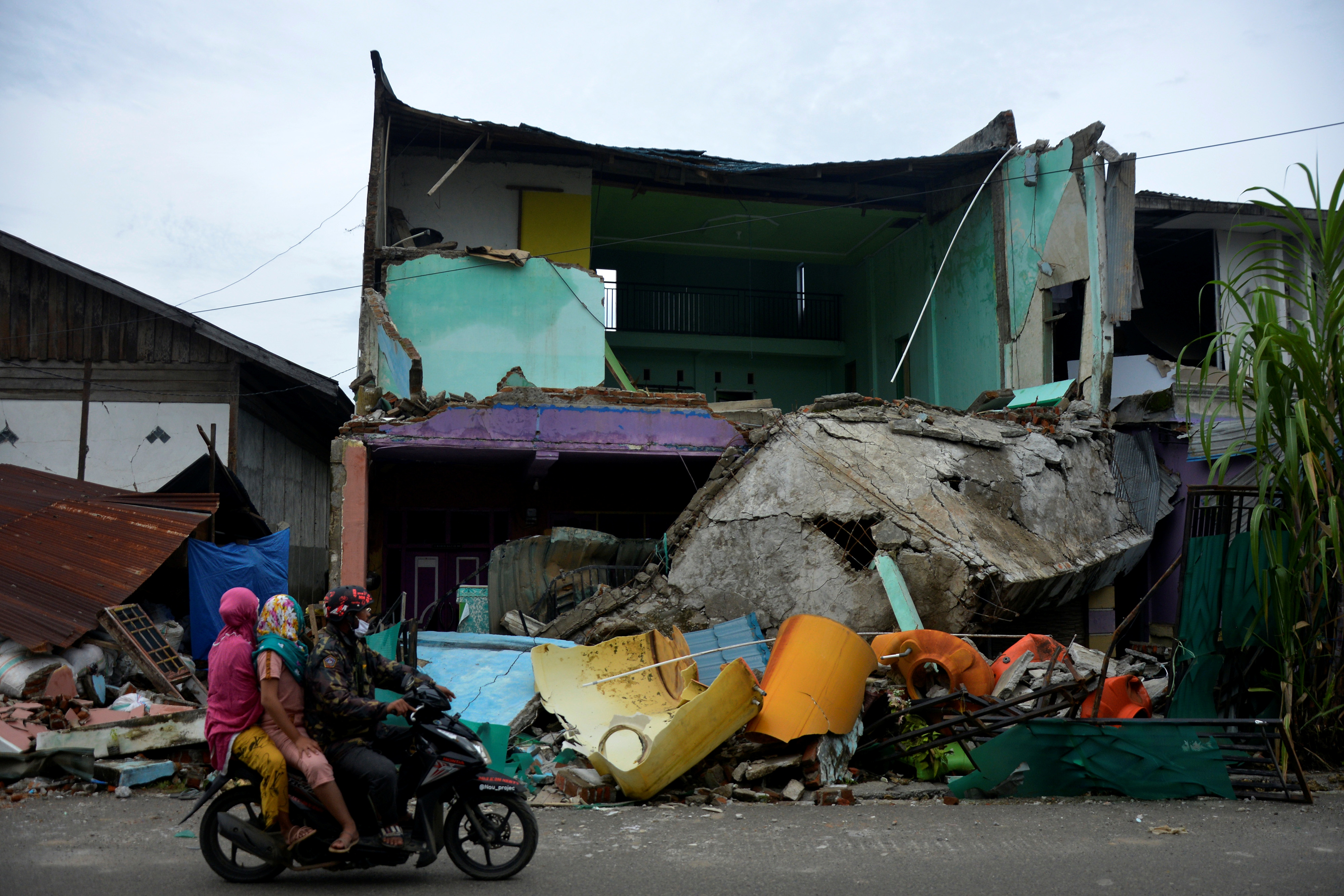 Locals ride a motorbike past a collapsed house following an earthquake in Mamuju, West Sulawesi province, Indonesia, January 17, 2021. Abriawan Abhe/Antara Foto via REUTERS