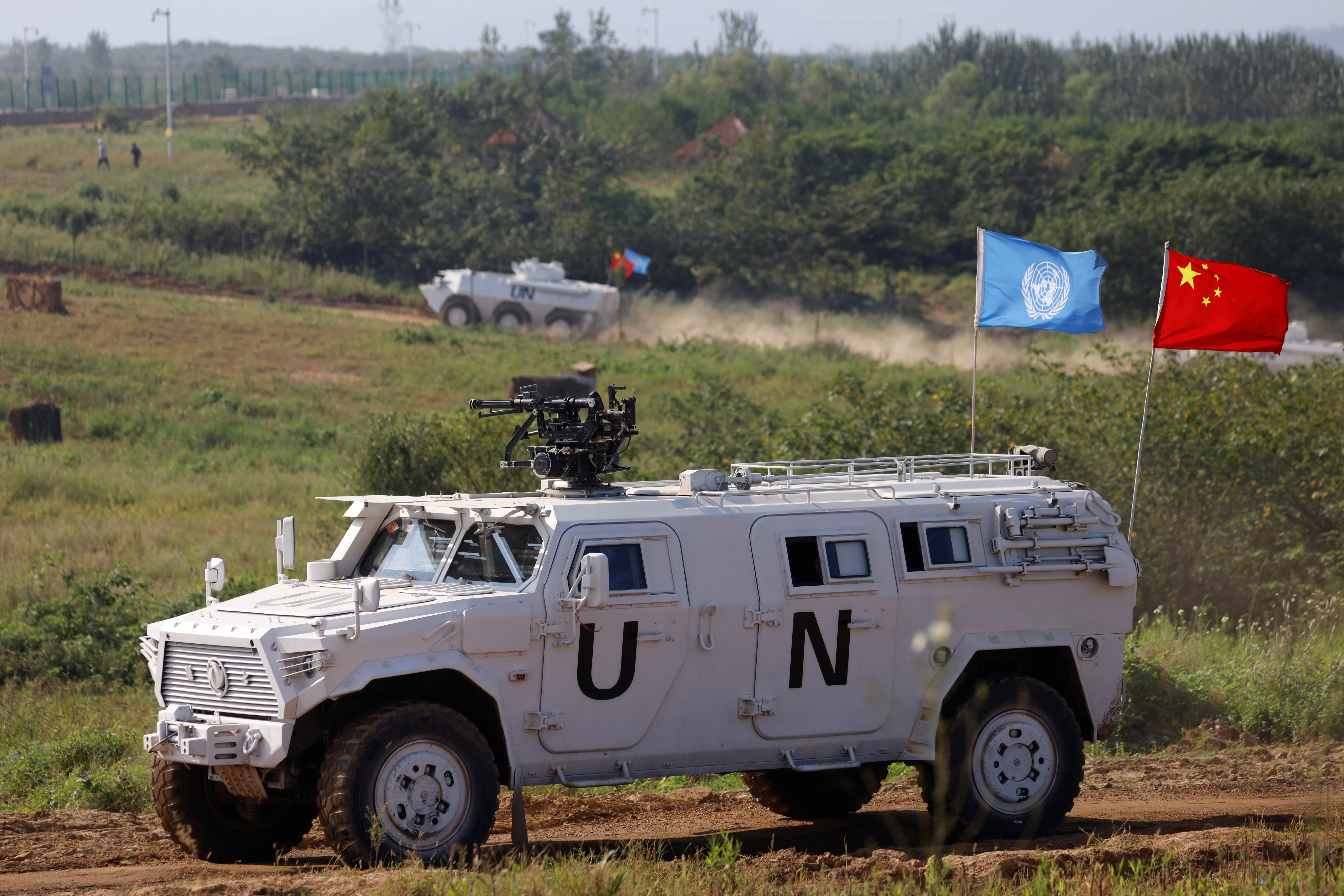 Armored vehicles with flags of the United Nations and China are seen during a multinational U.N. peacekeeping military exercise with troops of the Chinese People's Liberation Army (PLA), Pakistan, Mongolia and Thailand, on the outskirts of Zhumadian, Henan province, China September 15, 2021. REUTERS/Carlos Garcia Rawlins
