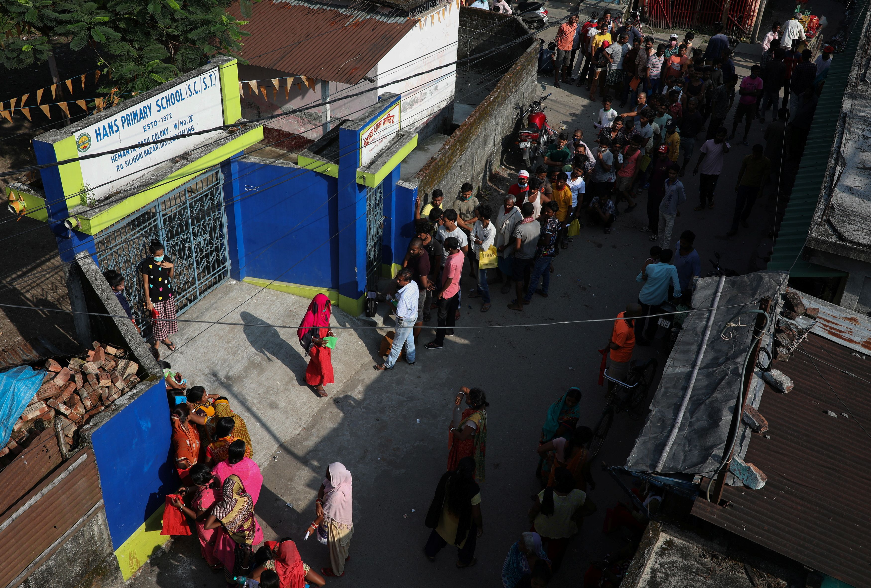 People stand in a queue to receive a dose of COVISHIELD vaccine,  manufactured by Serum Institute of India, outside a vaccination centre in Siliguri in the eastern state of West Bengal, India, October 7, 2021. Picture taken on October 7, 2021. REUTERS/Rupak De Chowdhuri