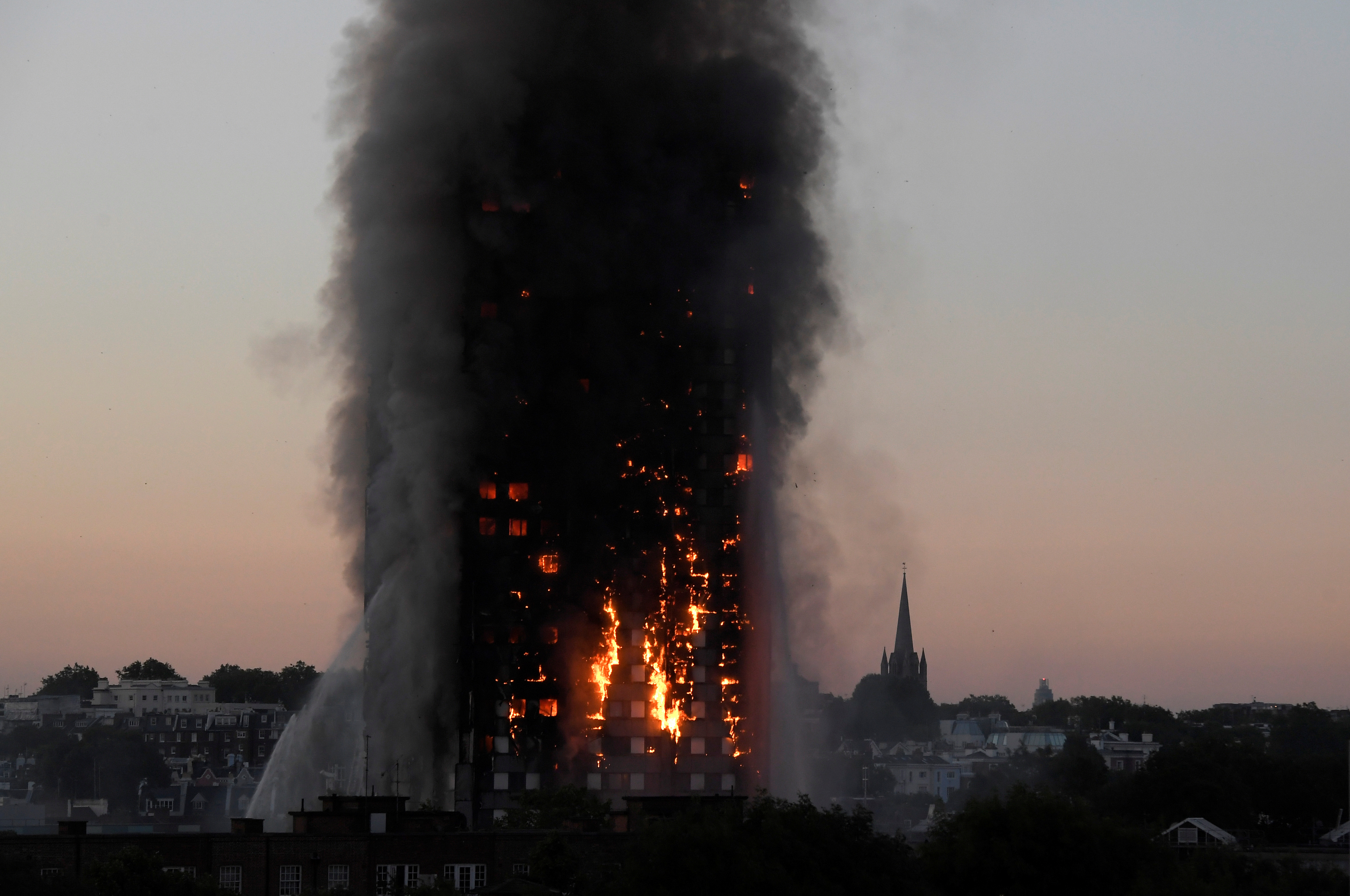 Flames and smoke billow as firefighters deal with a serious fire in the Grenfell Tower apartment block at Latimer Road in West London, Britain June 14, 2017. REUTERS/Toby Melville