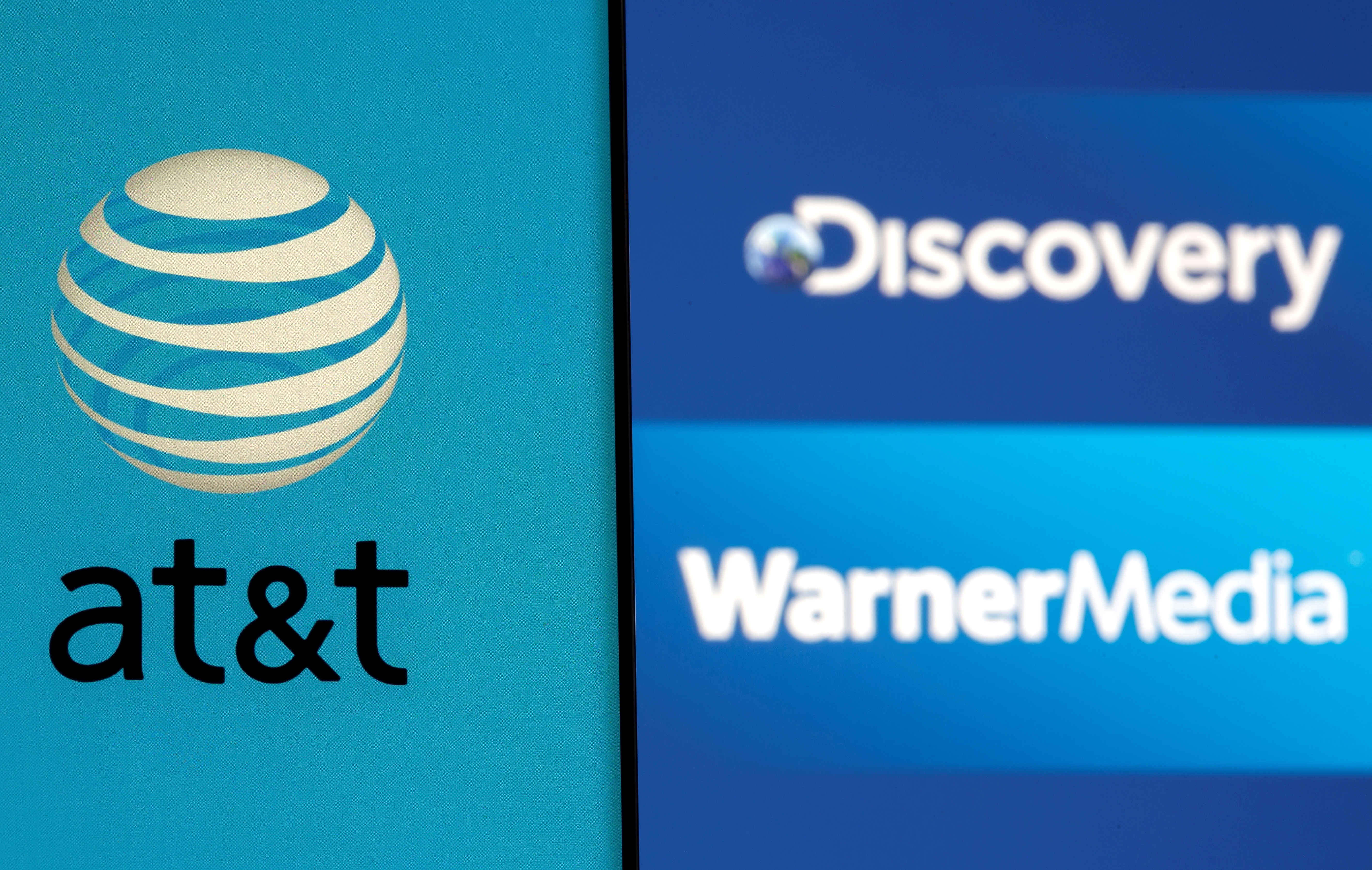 AT&T logo is seen on a smartphone in front of displayed Discovery and Warner Media logos in this illustration taken May 17, 2021. REUTERS/Dado Ruvic
