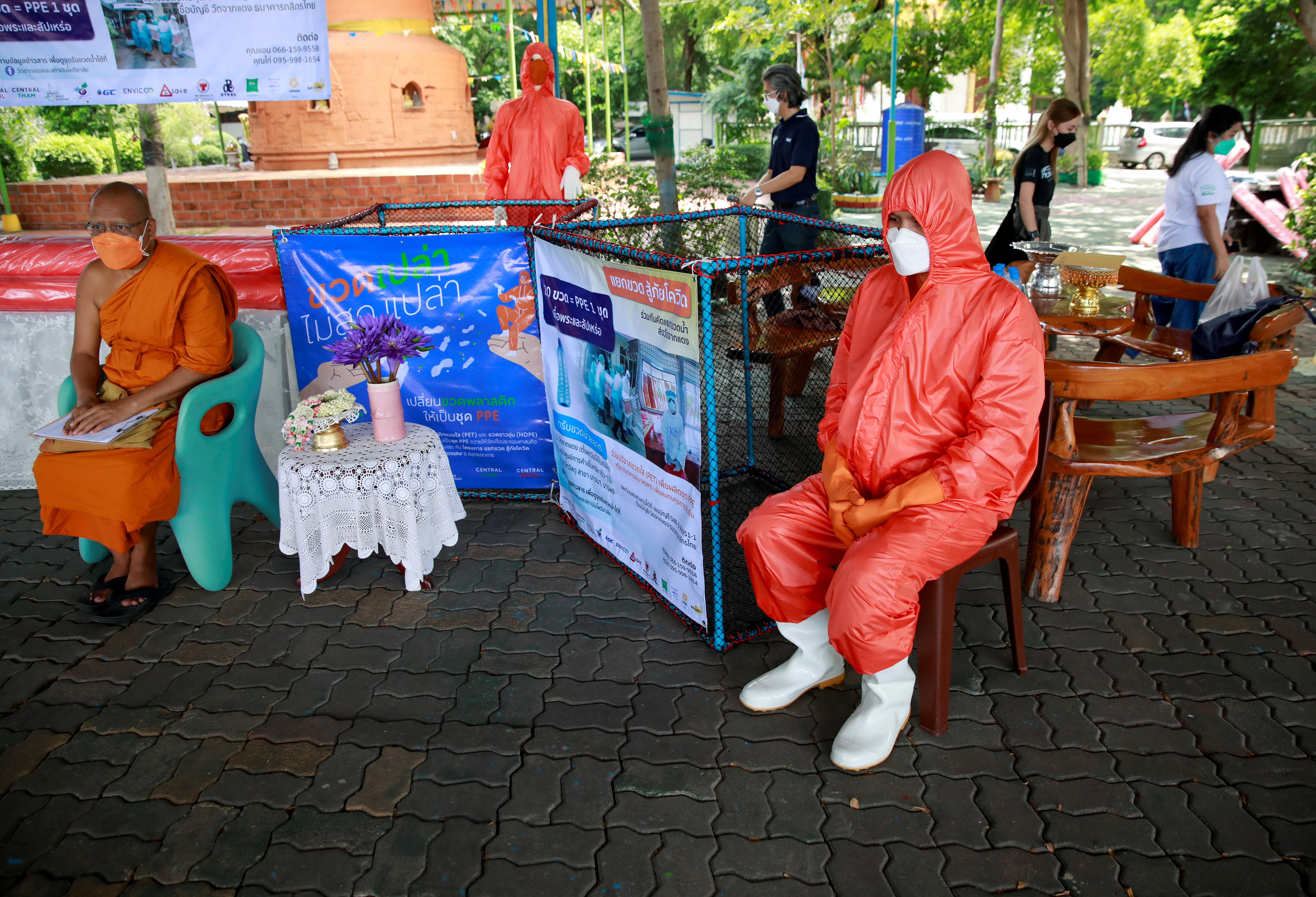 A Buddhist monk wears a PPE suit, as Bangkok city's administration and temples drive efforts to encourage the public to donate plastic bottles, which will be collected and upcycled into reusable Personal Protective Equipment (PPE) to reduce plastic waste as Thailand battles coronavirus disease (COVID-19) pandemic, in Bangkok, Thailand August 30, 2021. Picture taken August 30, 2021. REUTERS/Soe Zeya Tun