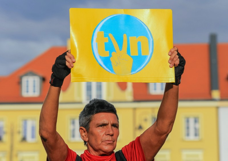 A protester holds a placard with the logo of the TVN Group during a demonstration in defence of media freedom and against a proposed amendment to the country's broadcast media law regarding the share of foreign capital in Polish media, in Bydgoszcz, Poland August 10, 2021. Roman Bosiacki/Agencja Gazeta/via REUTERS