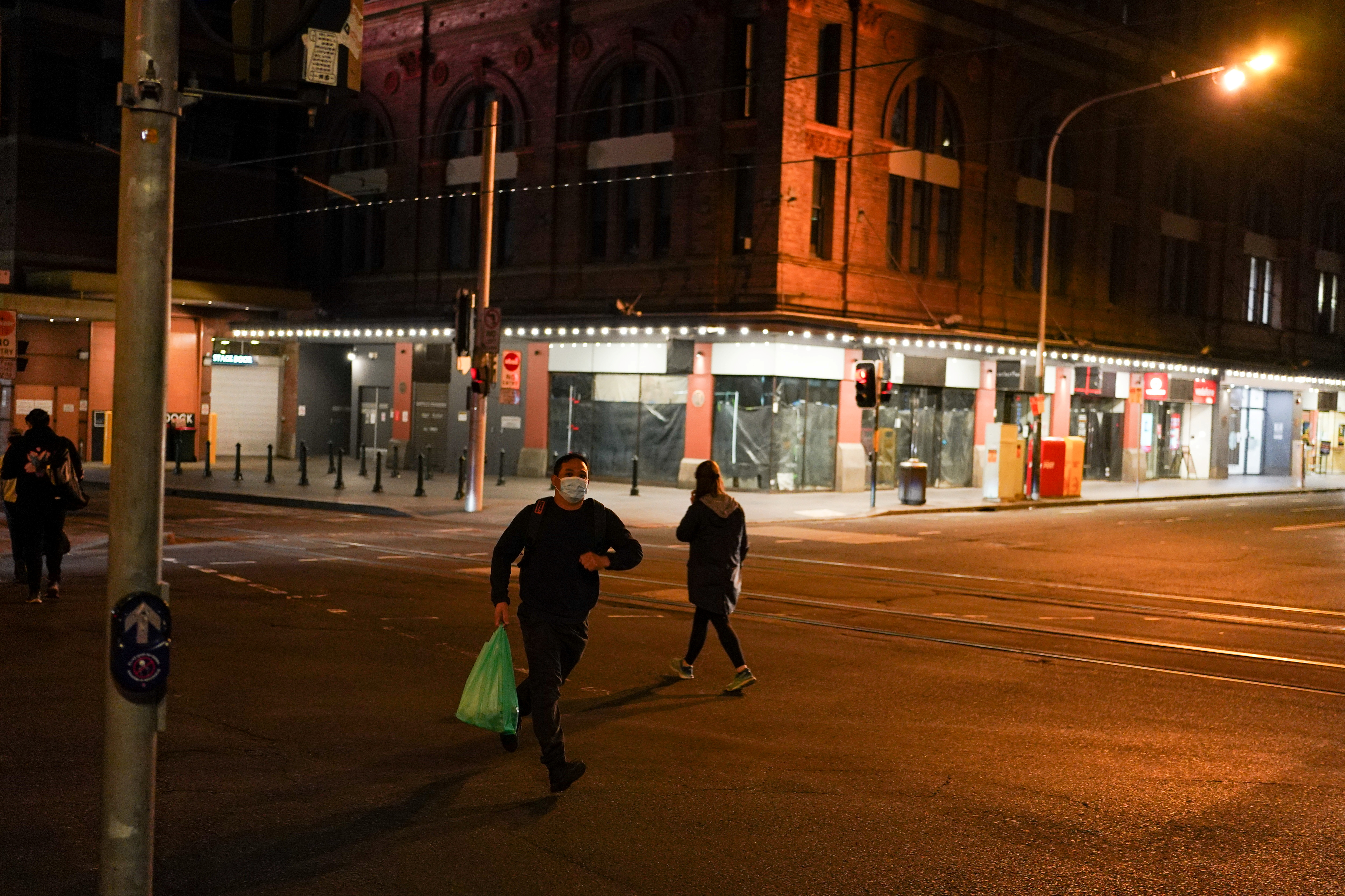A man wearing a protective face mask jogs across a quiet city centre street during a lockdown to curb the spread of a coronavirus disease (COVID-19) outbreak in Sydney, Australia, August 12, 2021.  REUTERS/Loren Elliott