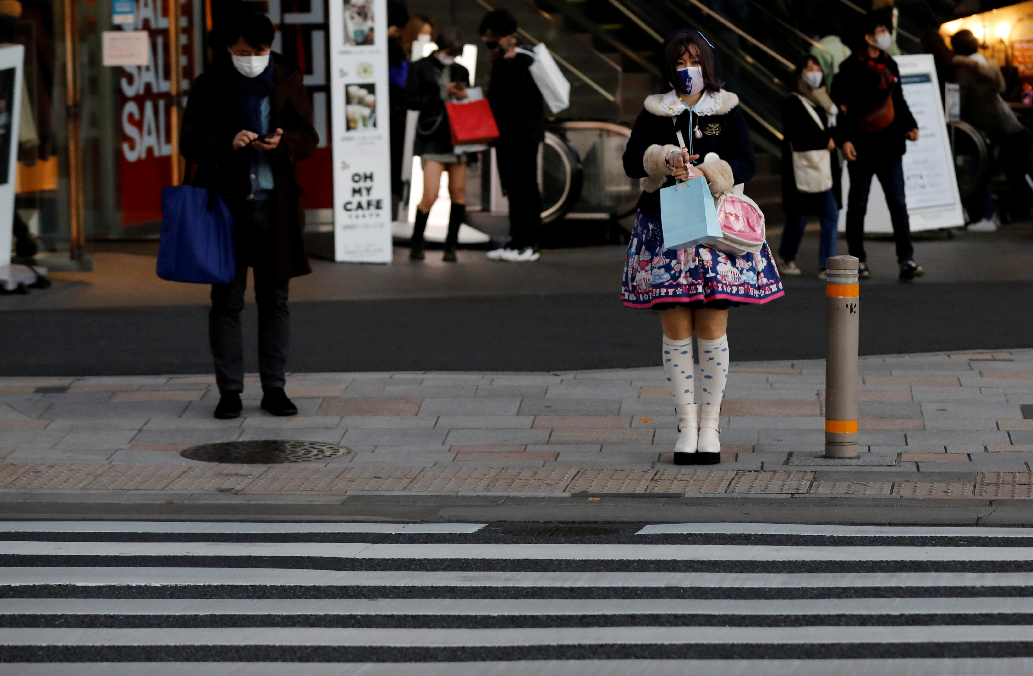 Pedestrians wearing protective masks amid the coronavirus disease (COVID-19) outbreak stand in front of a cross walk at a shopping district in Tokyo, Japan, December 17, 2020. REUTERS/Kim Kyung-Hoon