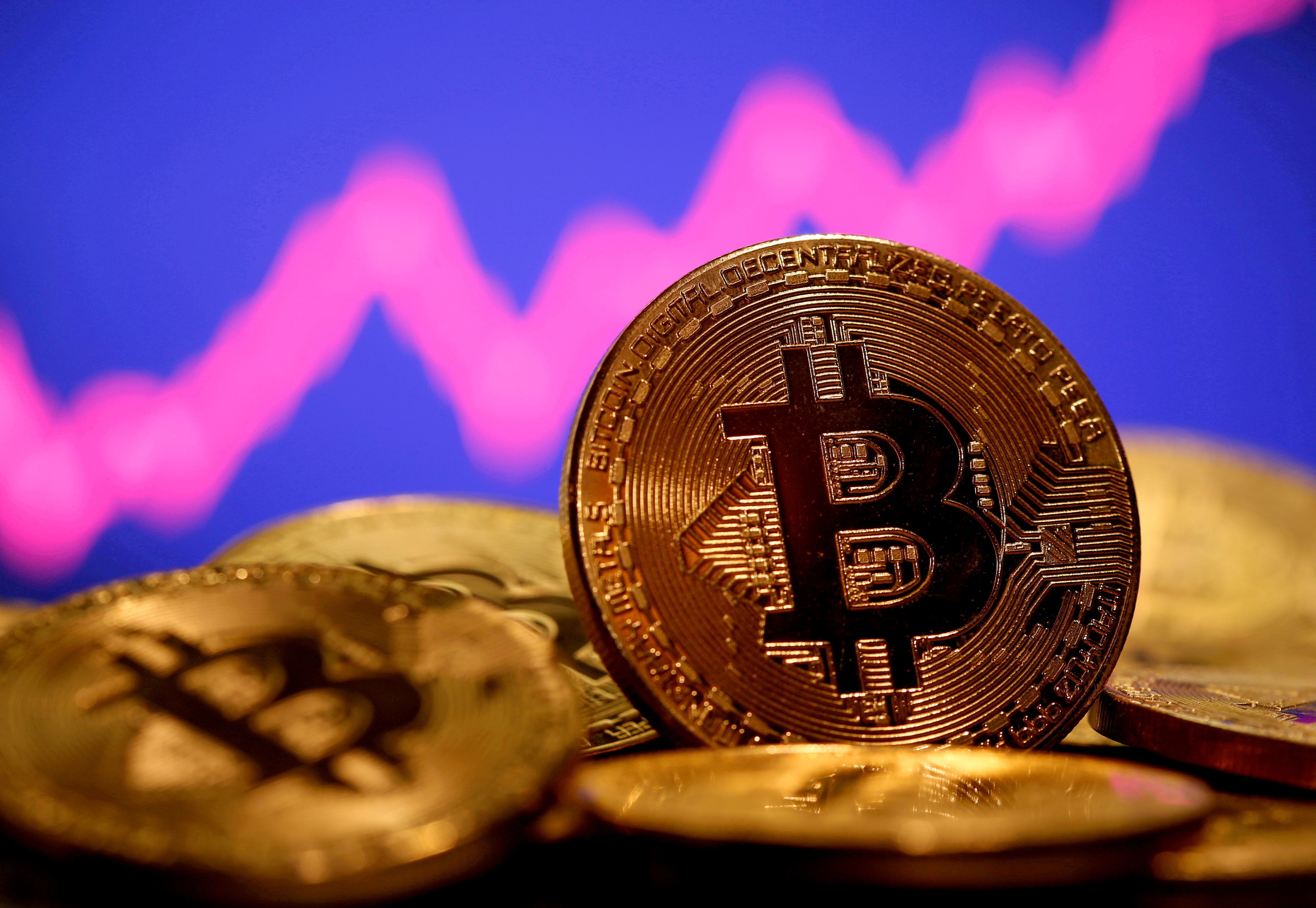A representation of virtual currency Bitcoin is seen in front of a stock graph in this illustration taken January 8, 2021. REUTERS/Dado Ruvic/File Photo
