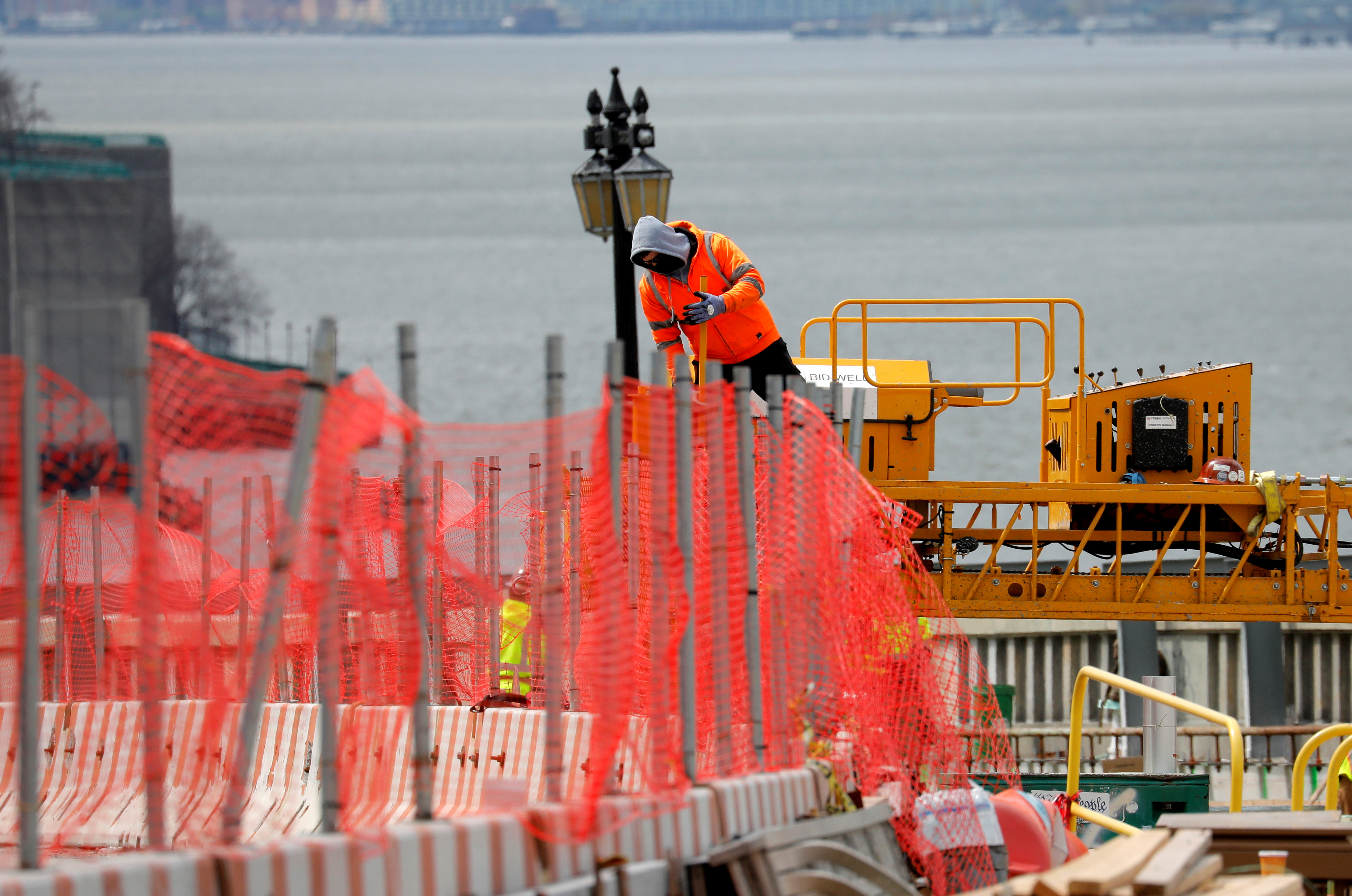 A construction worker climbs above a line of fencing at the site of a large public infrastructure reconstruction project of an elevated roadway and bridges in upper Manhattan in New York City, New York, U.S., April 22, 2021. REUTERS/Mike Segar