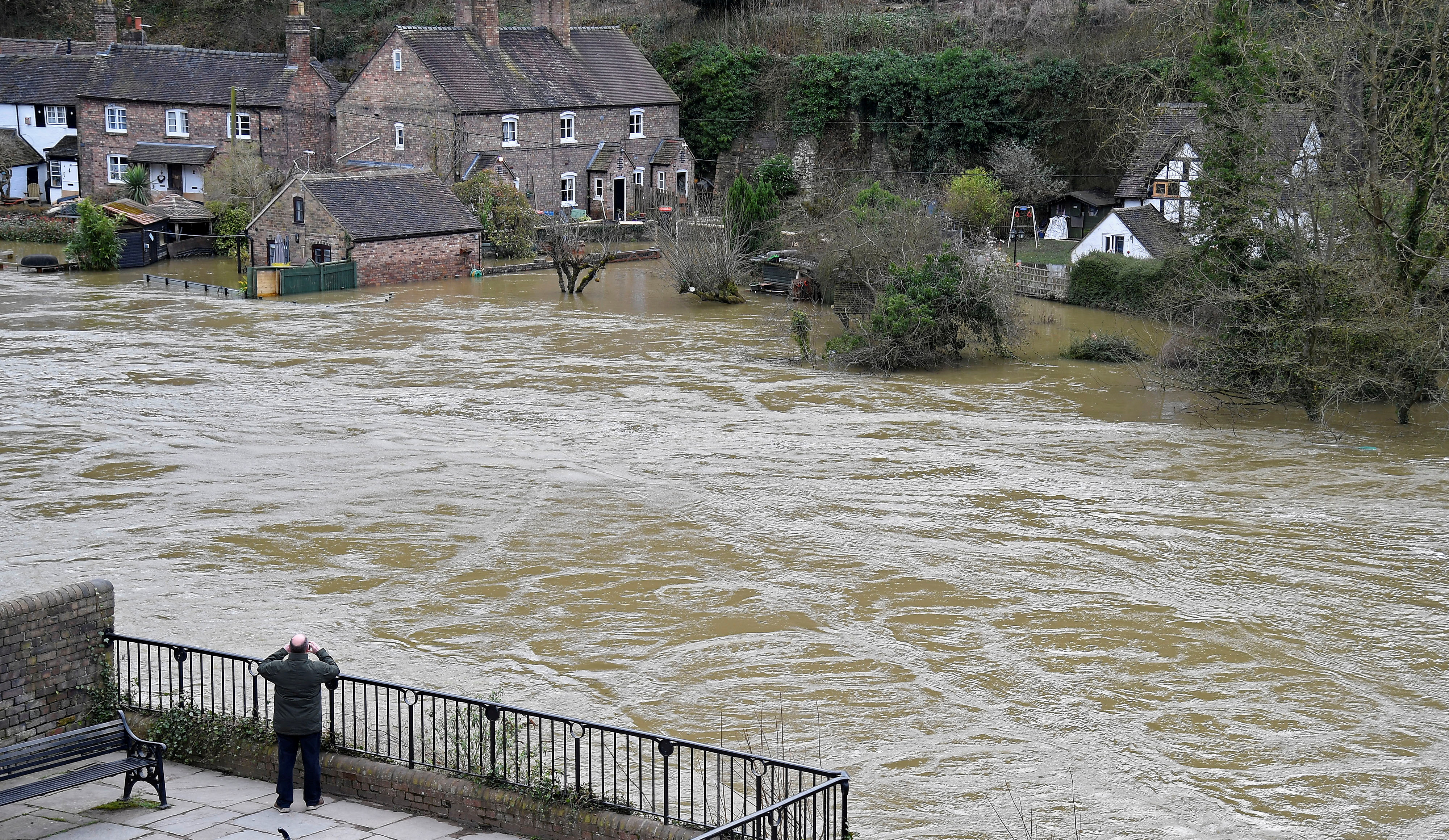 A man views flooded properties beside the River Severn in Ironbridge, Britain, February 27, 2020. REUTERS/Toby Melville