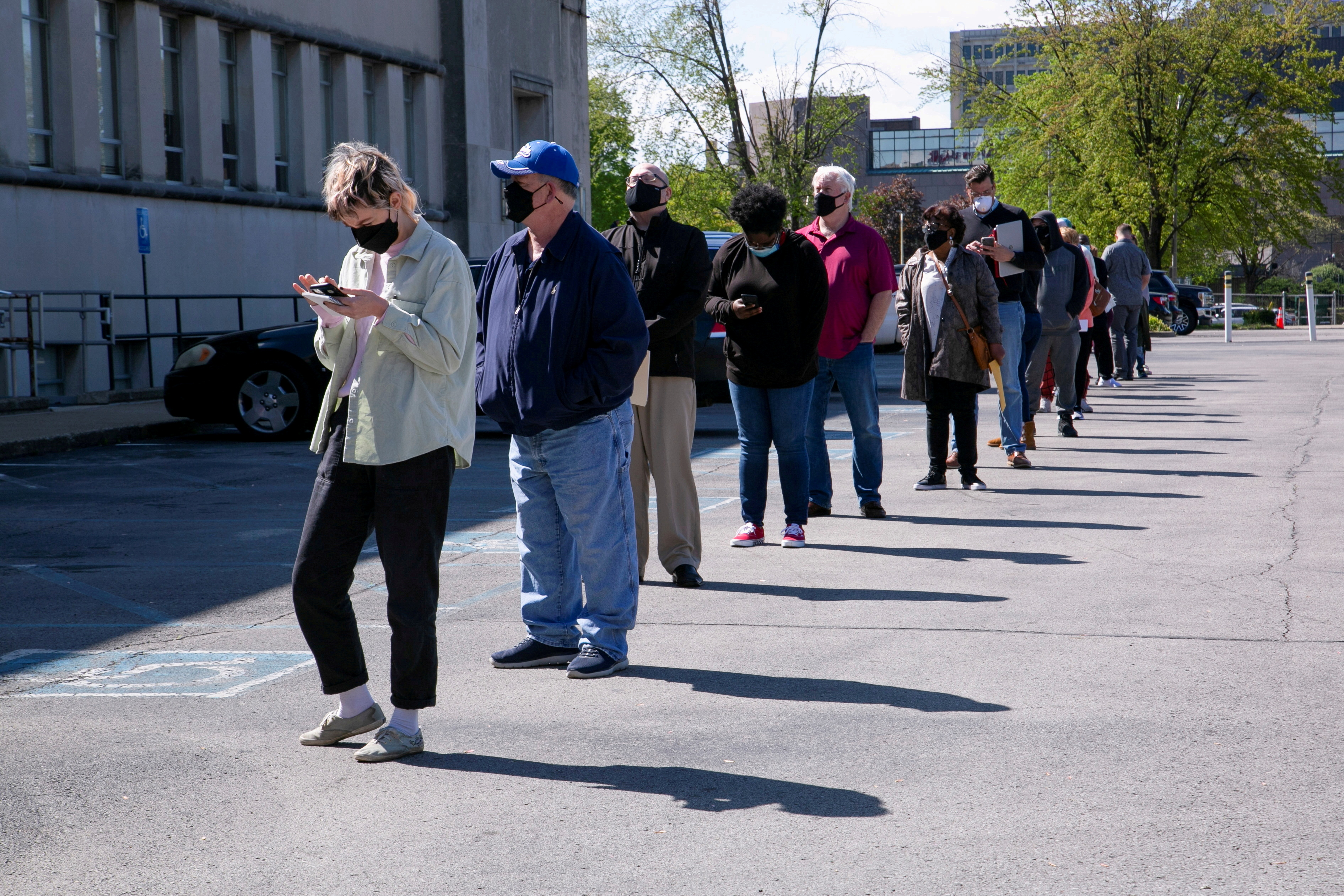 FILE PHOTO: People line up outside a newly reopened career center for in-person appointments in Louisville, U.S., April 15, 2021.  REUTERS/Amira Karaoud