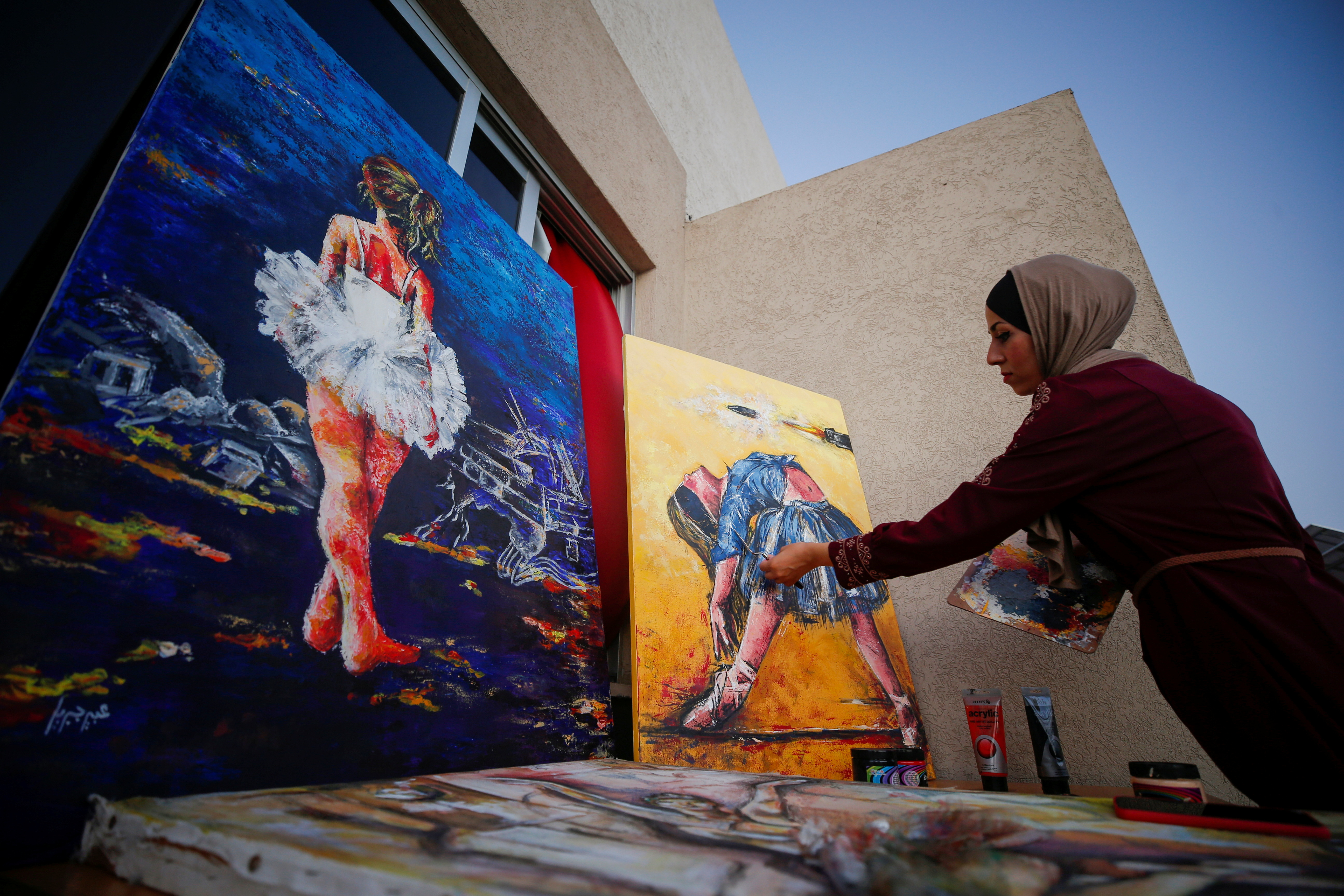 A Palestinian artist, Abeer Jibril, works on ballet paintings at her home in Gaza City, September 8, 2021. REUTERS/Mohammed Salem