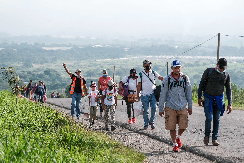 Hondurans walk along a road in a new caravan of migrants, set to head to the United States, in Naco, Honduras January 15, 2021. REUTERS/Yoseph Amaya