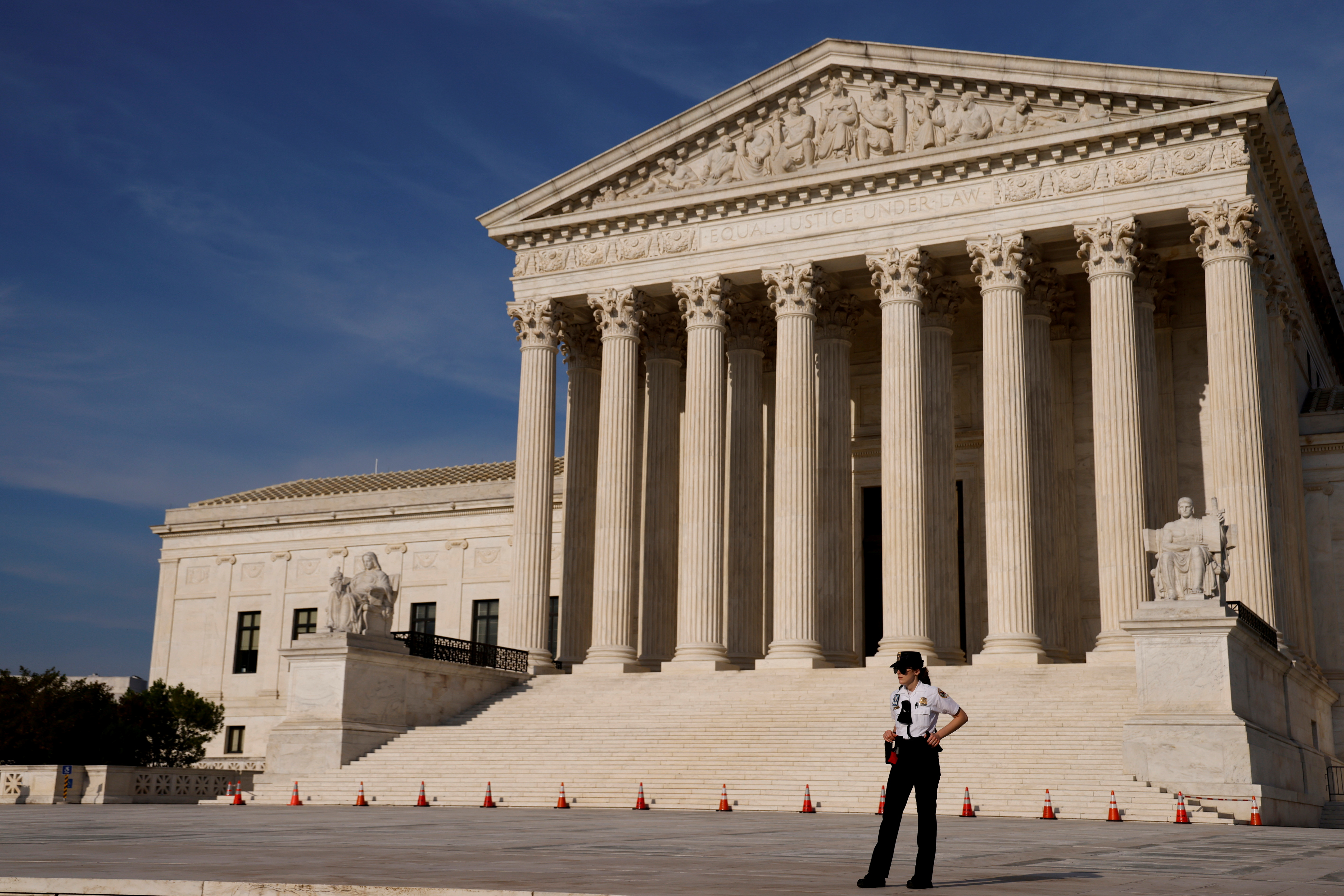 A U.S. Supreme Court police officer patrols the plaza in front the court building in Washington, U.S. May 17, 2021. REUTERS/Jonathan Ernst