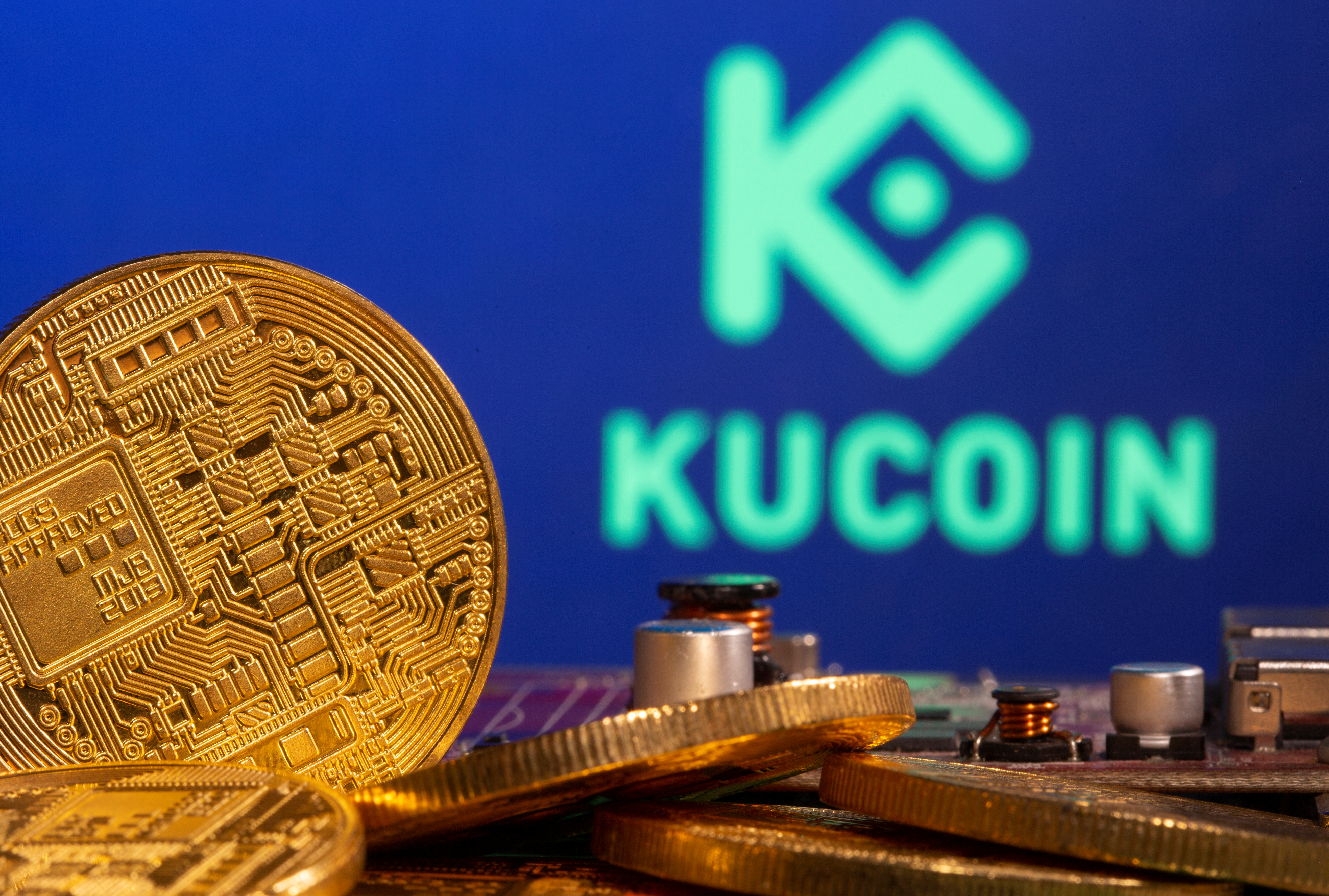 Representations of cryptocurrency is seen in front of a Kucoin logo in this illustration taken on February 9, 2021. REUTERS/Dado Ruvic/Illustration