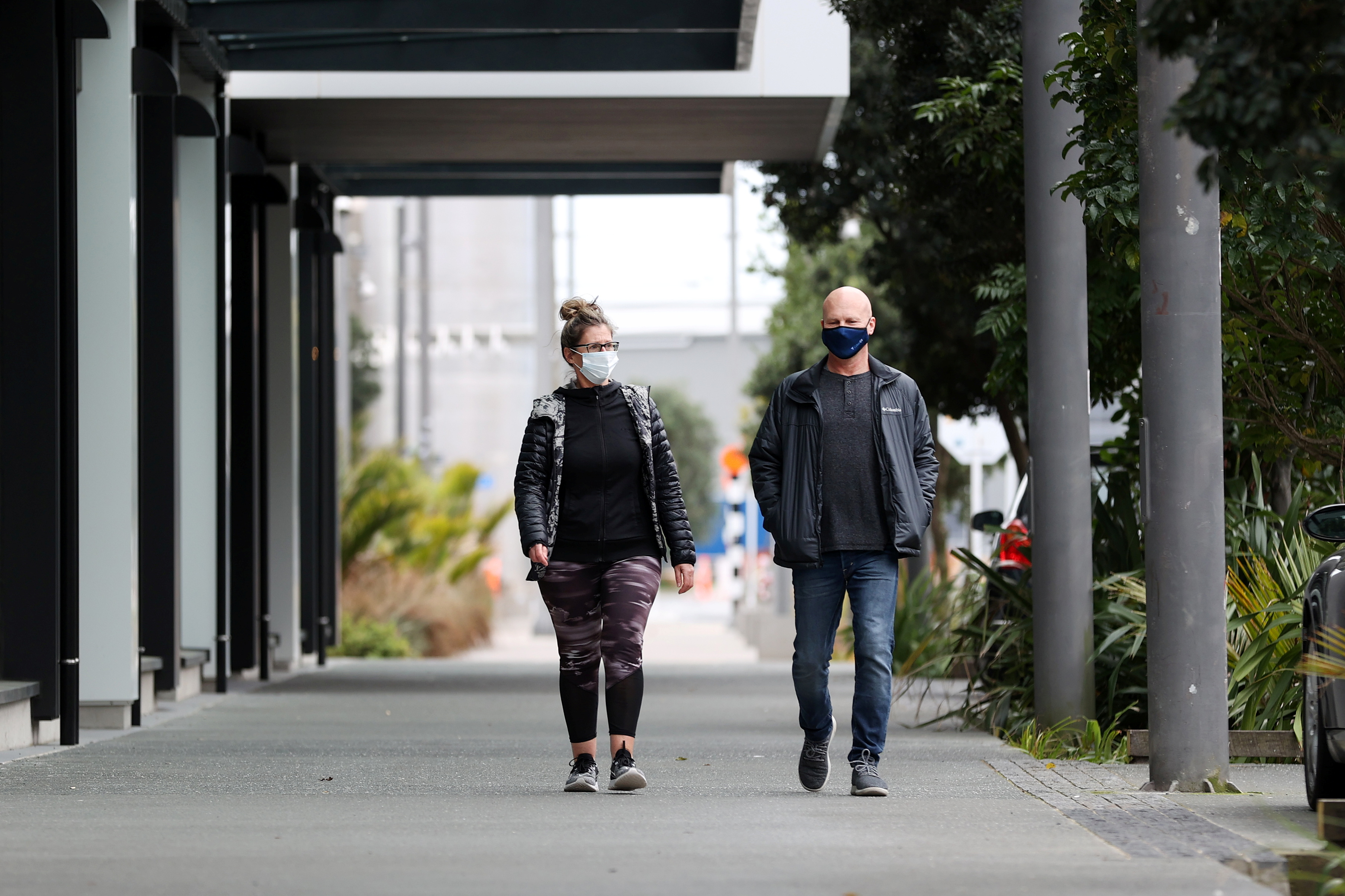 People wear masks as they exercise in the normally bustling Wynyard Wharf area on Auckland's waterfront during a lockdown to curb the spread of a coronavirus disease (COVID-19) outbreak, in Auckland, New Zealand, August 26, 2021.  REUTERS/Fiona Goodall