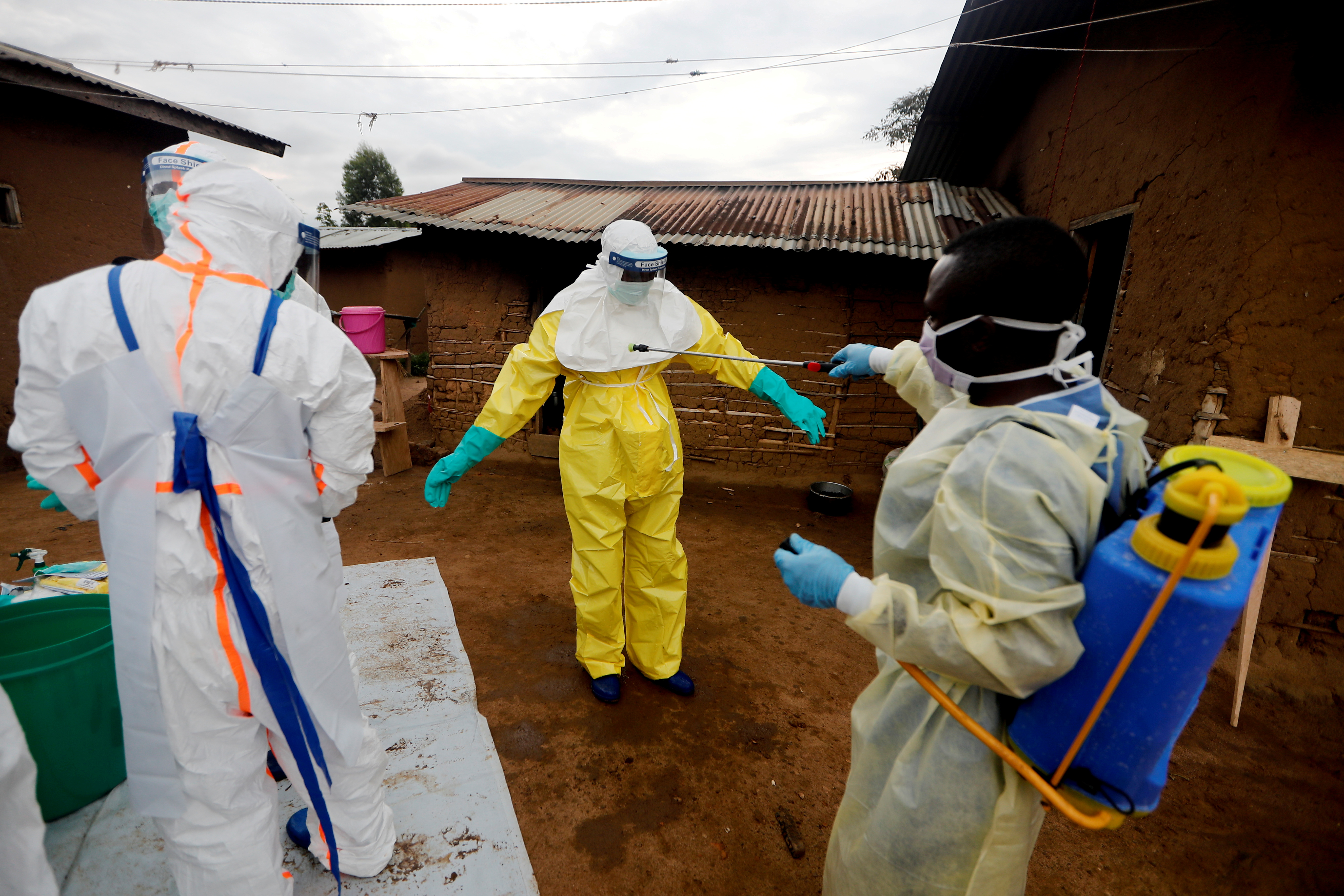 Kavota Mugisha Robert, a healthcare worker, who volunteered in the Ebola response, decontaminates his colleague after he entered the house of 85-year-old woman, suspected of dying of Ebola, in the eastern Congolese town of Beni in the Democratic Republic of Congo, October 8, 2019. REUTERS/Zohra Bensemra/File Photo