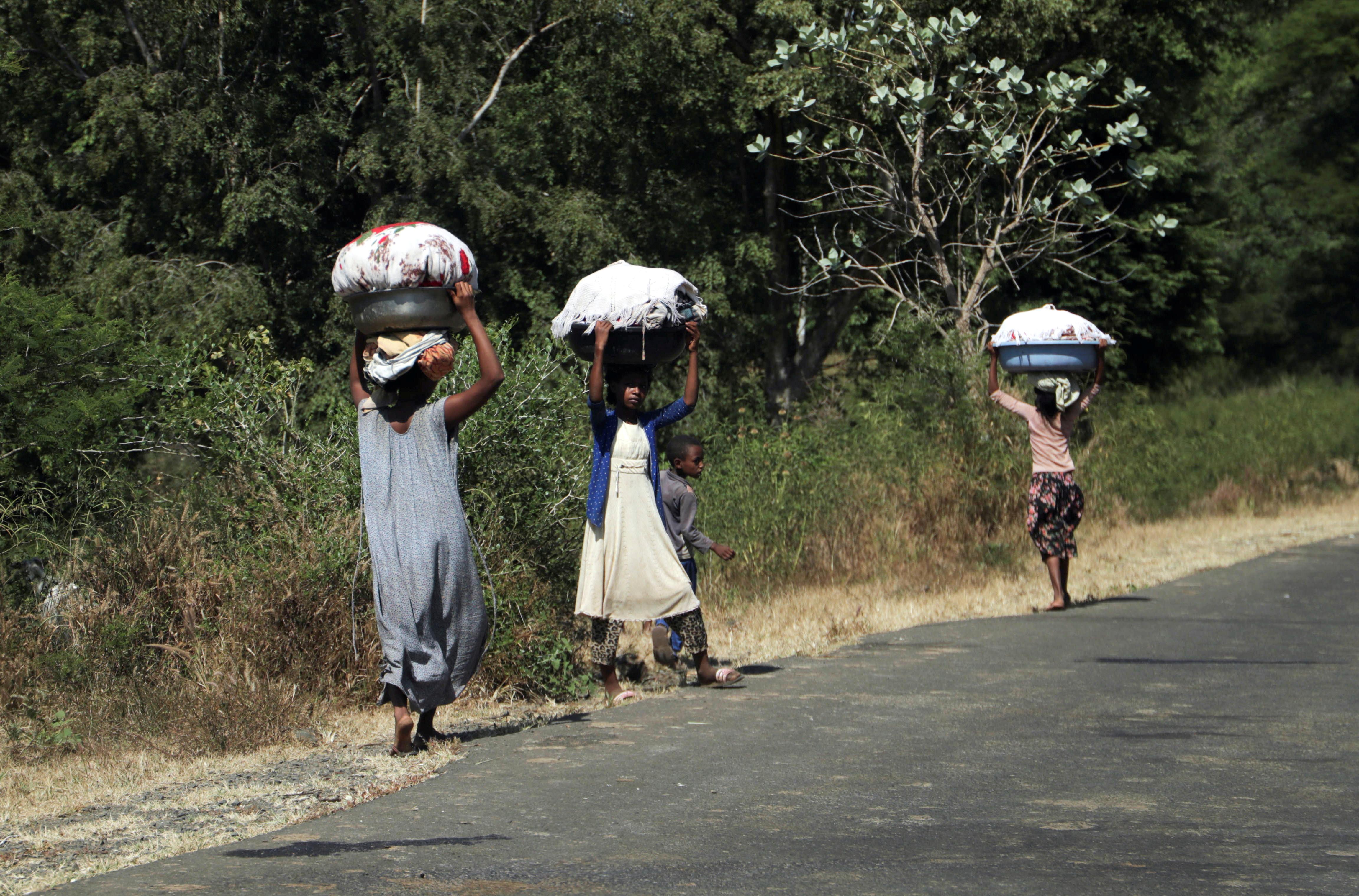 Girls carry laundry in Soroka town in Amhara region near a border with Tigray, Ethiopia November 9, 2020. REUTERS/Tiksa Negeri/File Photo