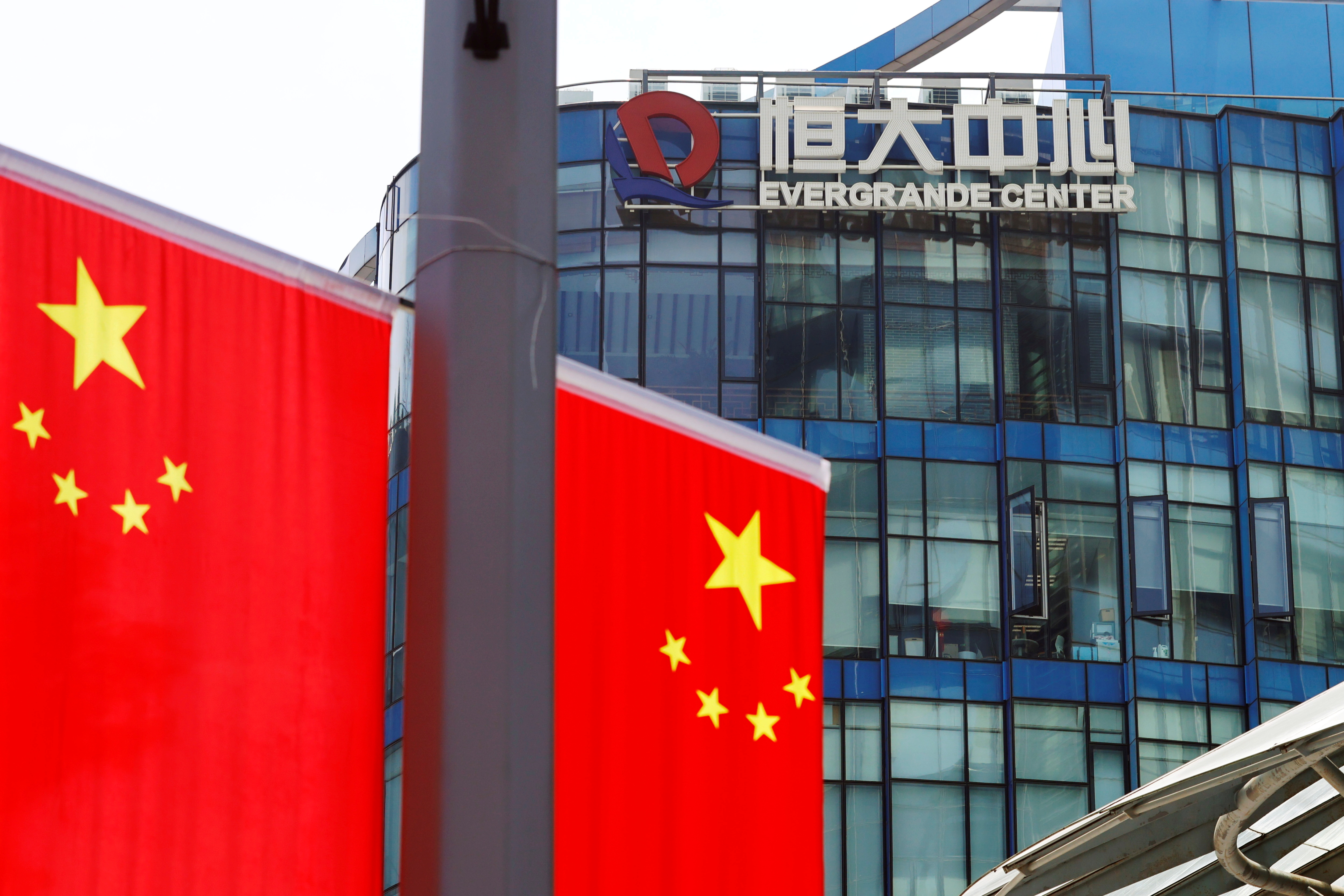 Chinese flags are seen near the logo of the China Evergrande Group on the Evergrande Center in Shanghai, China, September 24, 2021. REUTERS/Aly Song/File Photo