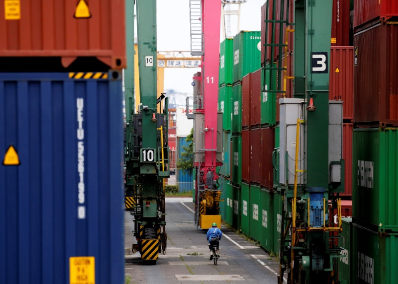 A man in a bicycle drives past containers at an industrial port in Tokyo, Japan, May 22, 2019. REUTERS/Kim Kyung-Hoon