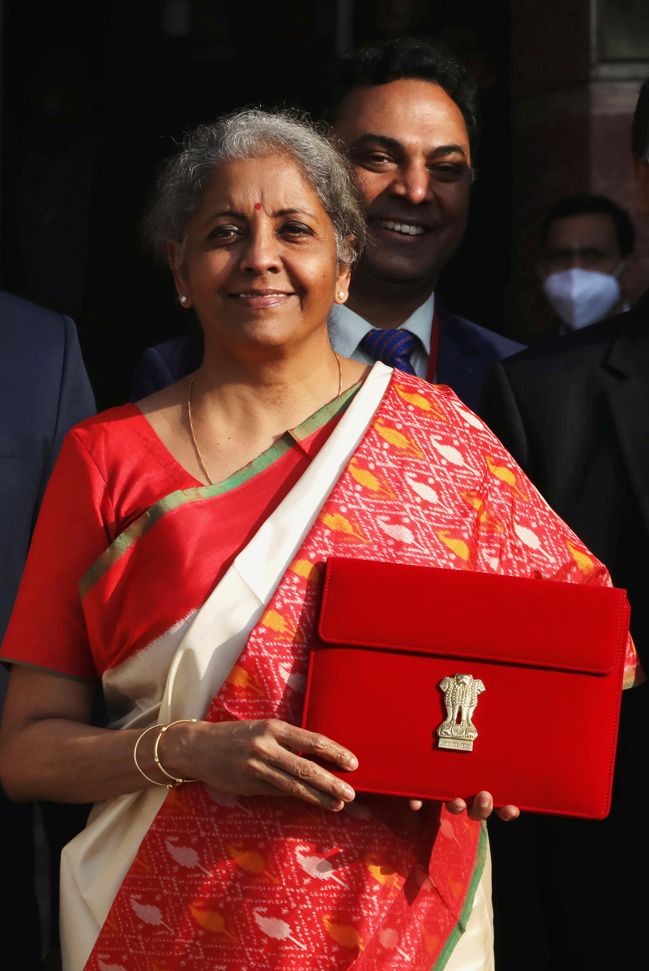 India's Finance Minister Nirmala Sitharaman holds up a folder with the Government of India logo, while India's Chief Economic Advisor Krishnamurthy Subramanian looks on (at rear), as she leaves her office to present the federal budget in the parliament in New Delhi, India, February 1, 2021. REUTERS/Anushree Fadnavis
