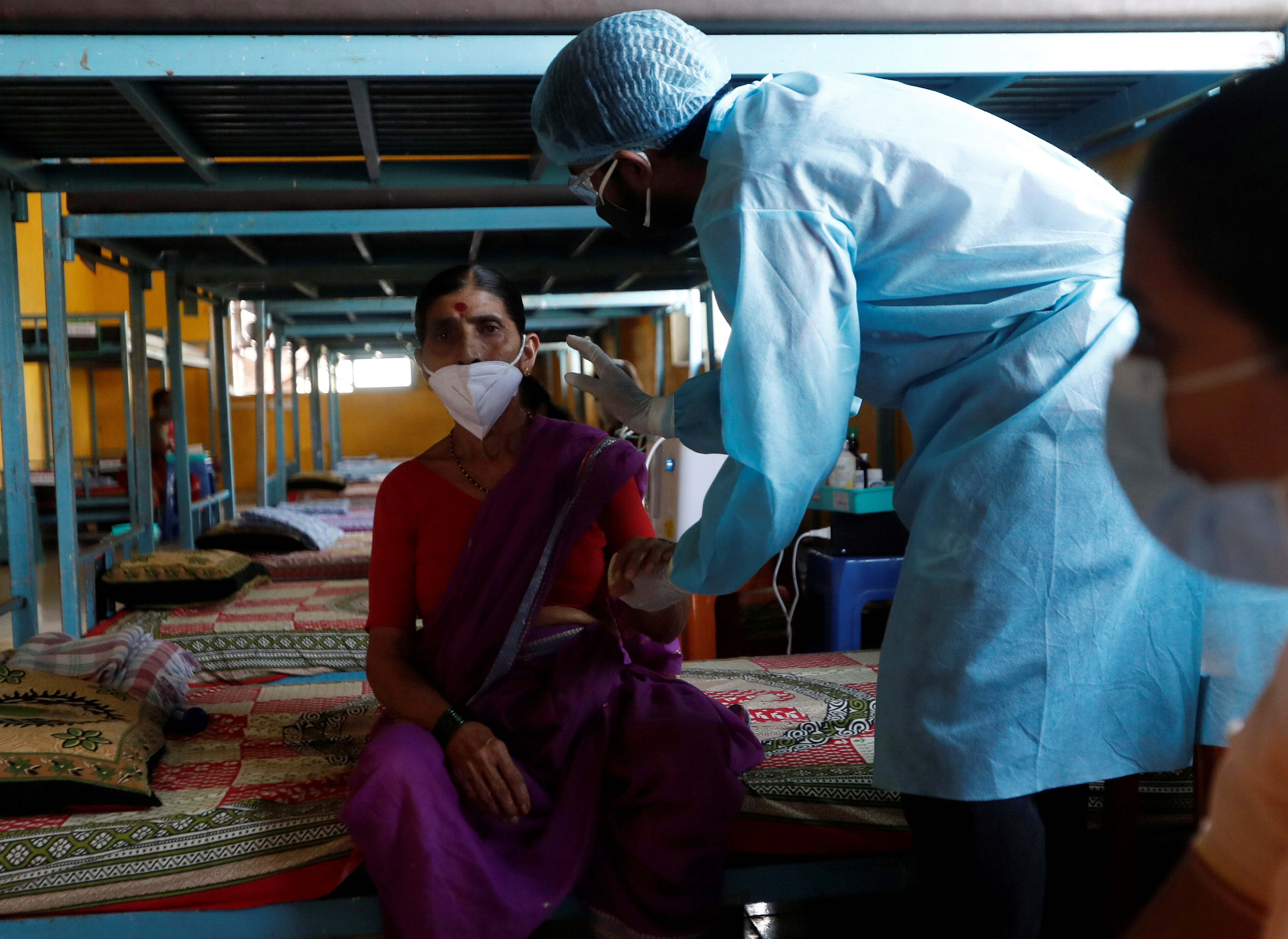 A doctor inspects a patient suffering from coronavirus disease (COVID-19) inside the classroom turned COVID-19 care facility on the outskirts of Mumbai, India, May 24, 2021. REUTERS/Francis Mascarenhas