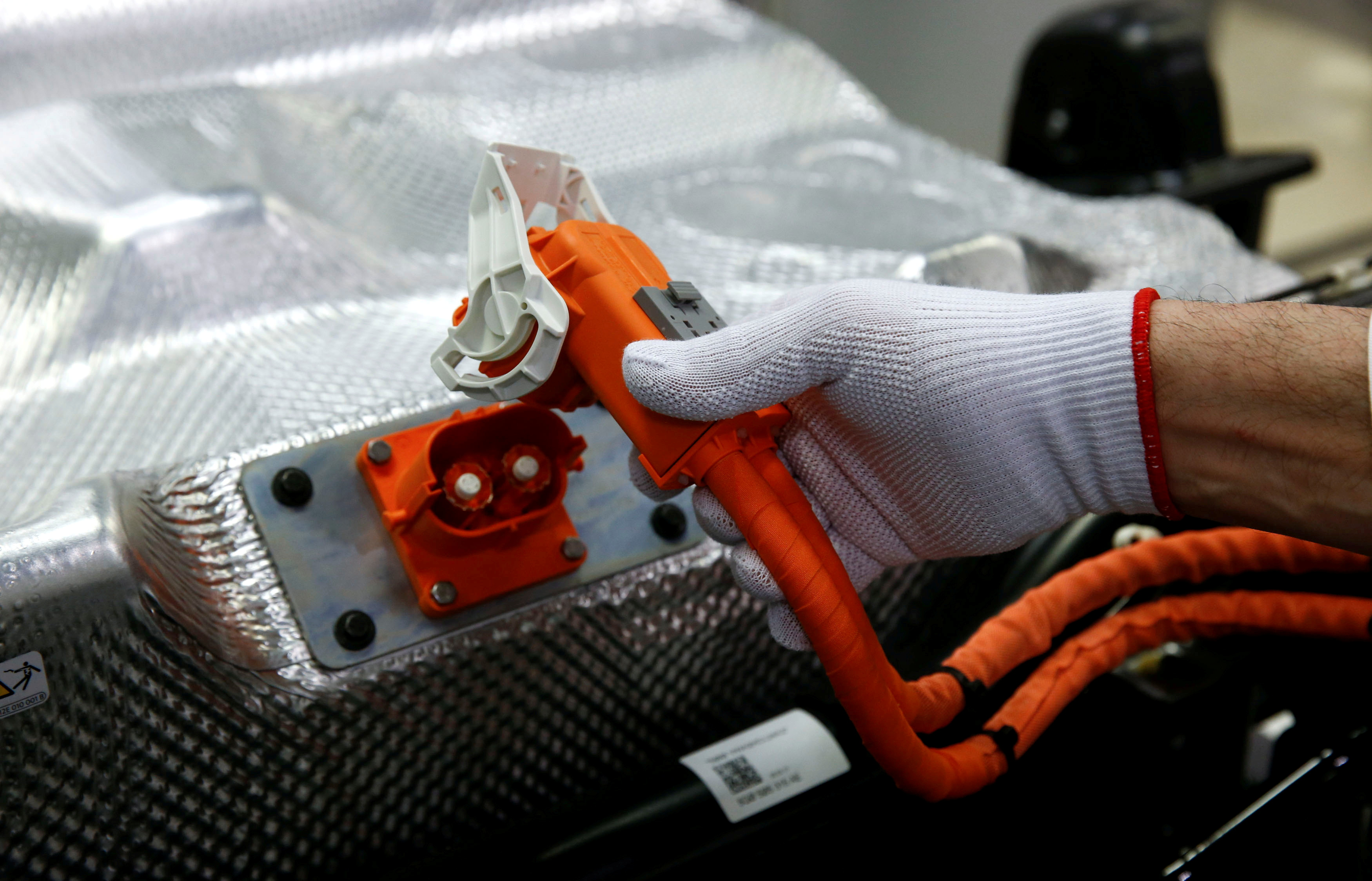 A worker connects the battery during the assembly of an e-Golf electric car at the new production line of the Transparent Factory of German carmaker Volkswagen in Dresden, Germany March 30, 2017. REUTERS/Fabrizio Bensch
