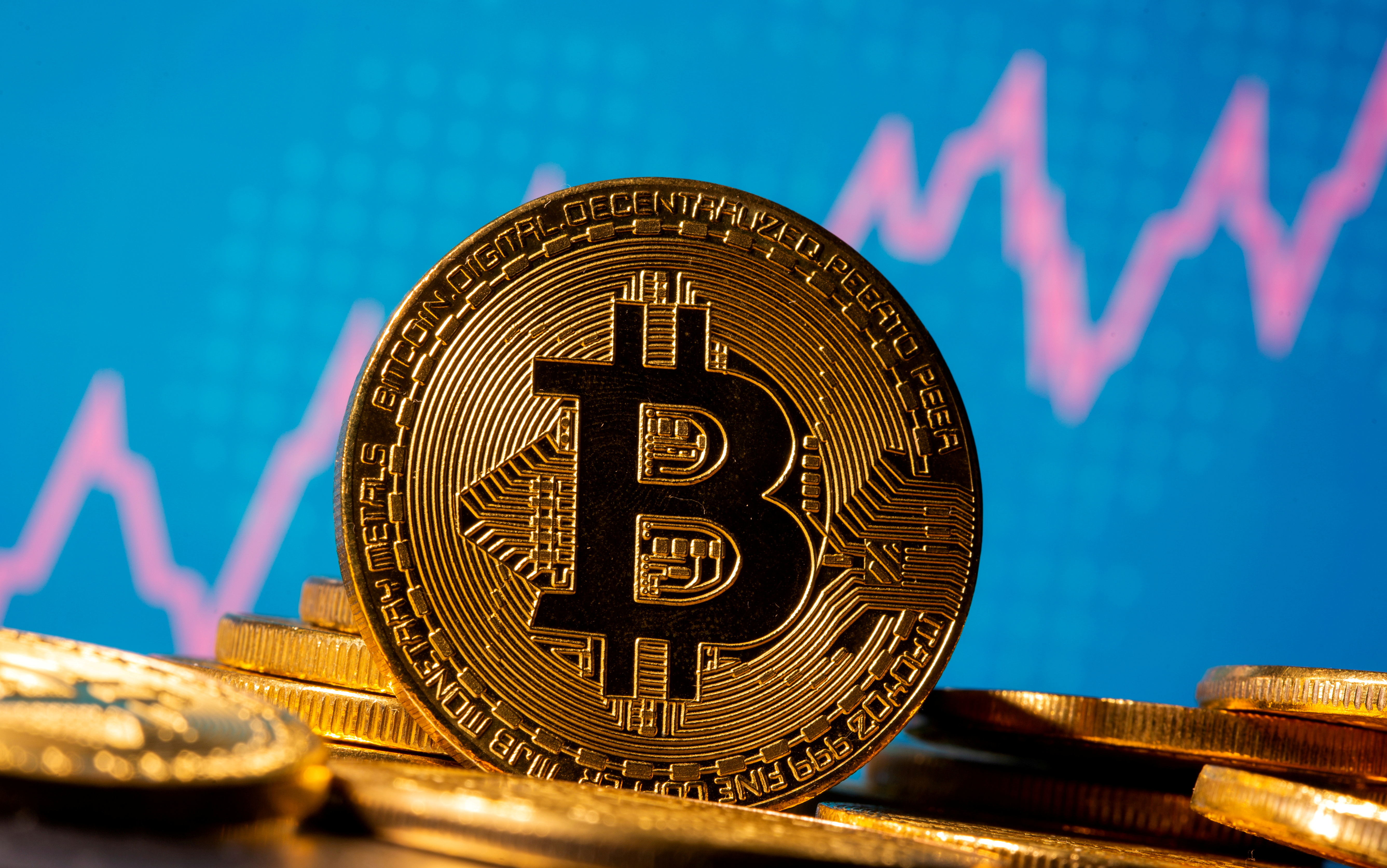 A representation of virtual currency bitcoin is seen in front of a stock graph in this illustration taken November 19, 2020. REUTERS/Dado Ruvic/Illustration
