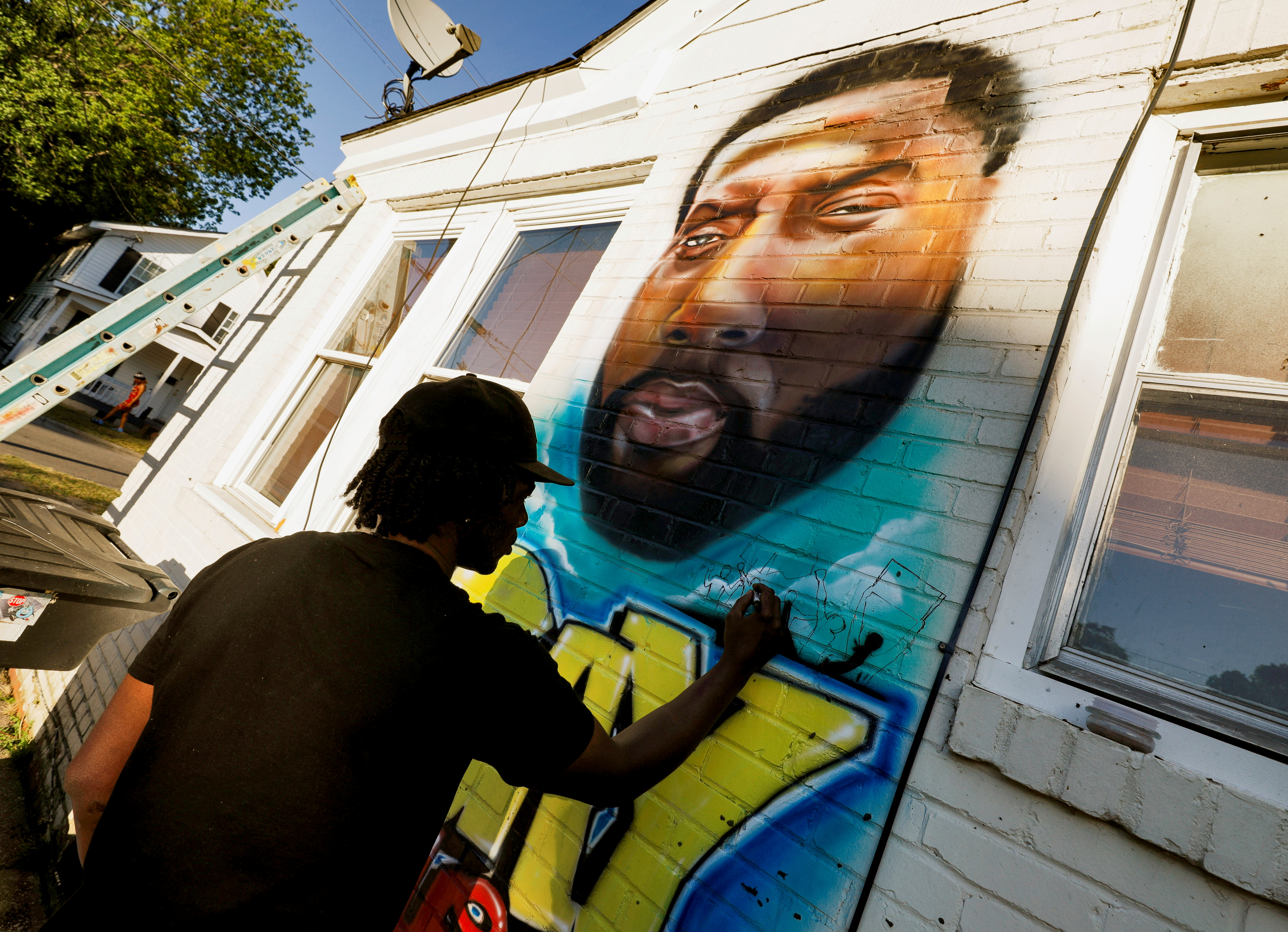 Ulysses Edwards, a friend of Andrew Brown Jr., finishes a mural in his honor at the site where sheriff's deputies killed Brown in Elizabeth City, North Carolina, U.S. May 1, 2021. REUTERS/Jonathan Drake