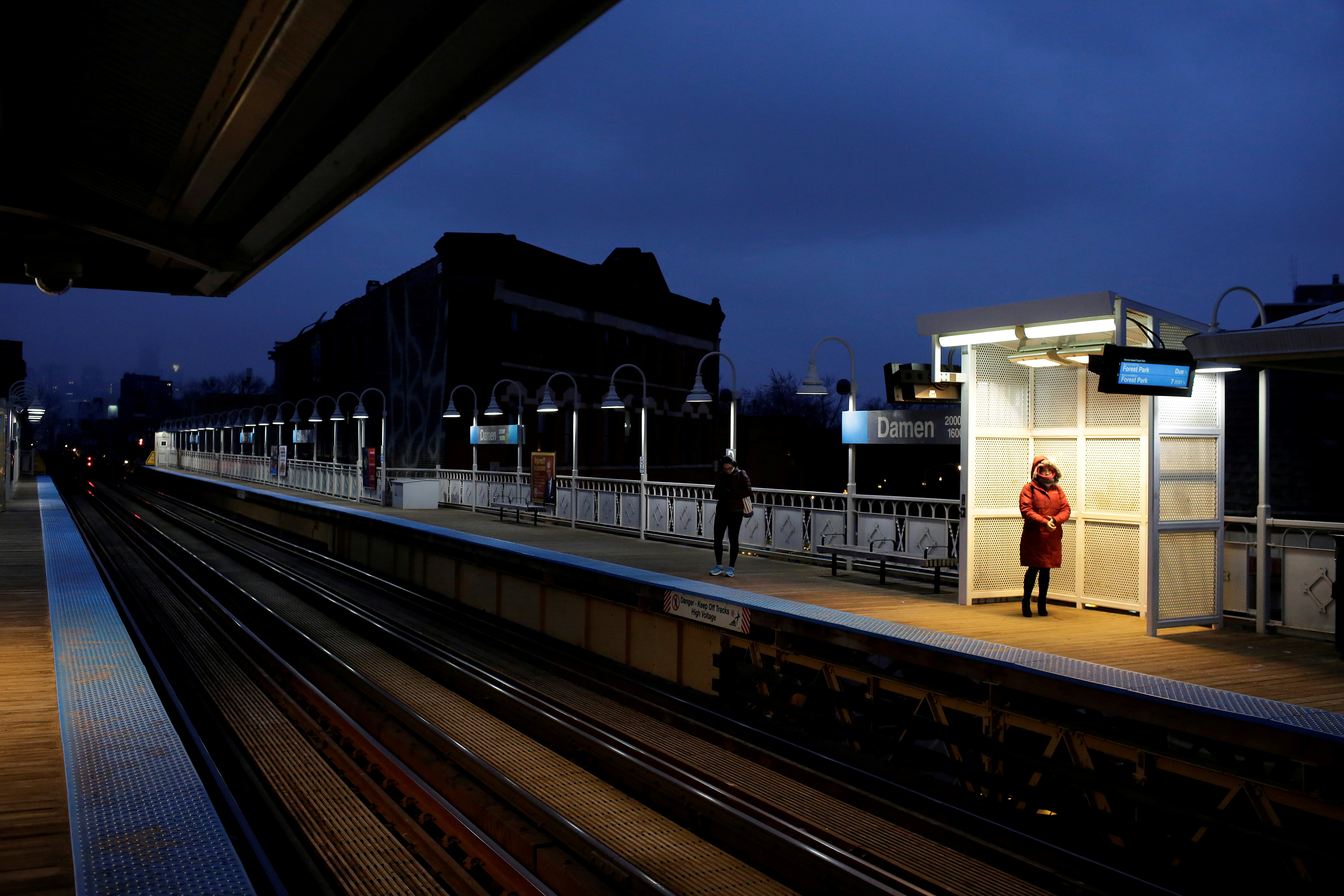 Commuters wait for the Chicago Transit Authority Blue line train at the Damen Avenue stop in Chicago, Illinois, U.S. March 16, 2020. REUTERS/Joshua Lott