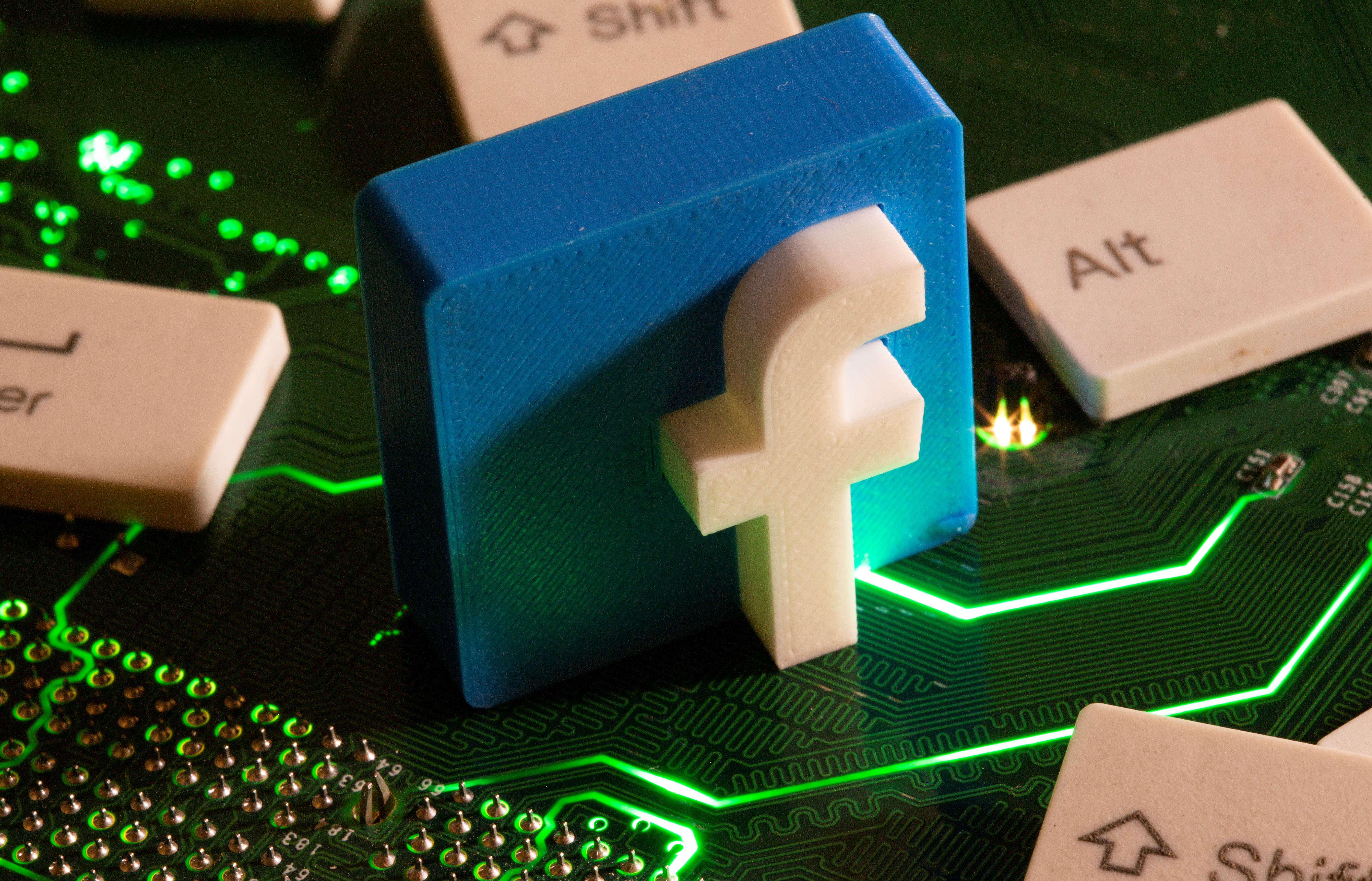A 3D printed Facebook logo and keyboard buttons are placed on a computer motherboard in this illustration taken January 21, 2021. REUTERS/Dado Ruvic/Illustration