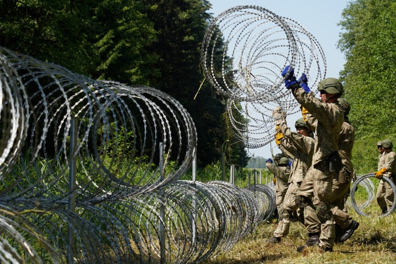 Lithuanian army soldiers install razor wire on the border with Belarus in Druskininkai, Lithuania July 9, 2021. REUTERS/Janis Laizans/File Photo