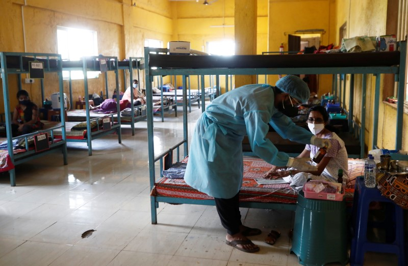 A doctor checks the medicines of a patient suffering from coronavirus disease (COVID-19) inside a classroom turned COVID-19 care facility on the outskirts of Mumbai, India, May 24, 2021. REUTERS/Francis Mascarenhas