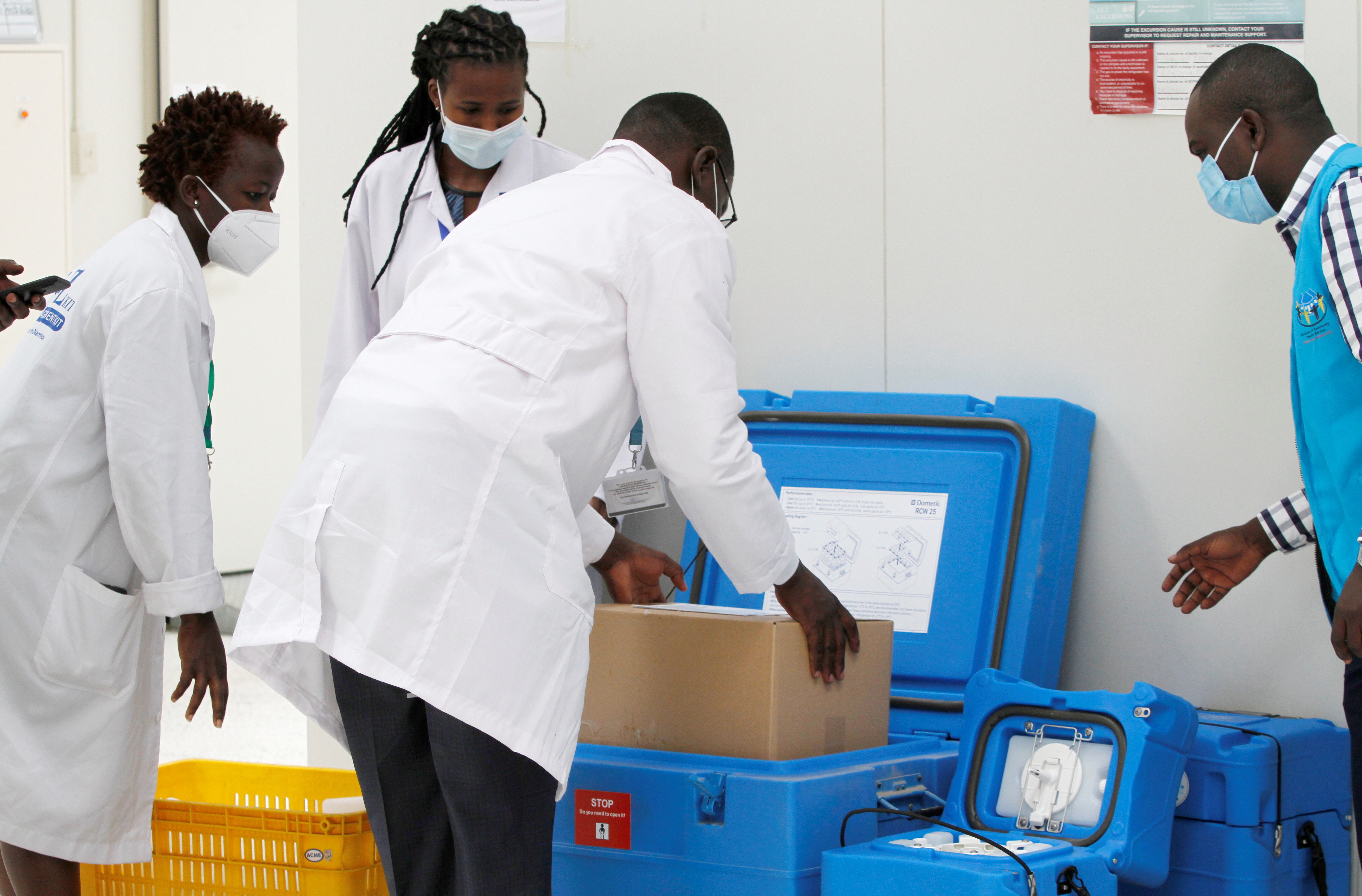 Biomedical engineers pack a consignment of AstraZeneca/Oxford vaccines under the COVAX scheme against coronavirus disease (COVID-19), before distribution at the Kitengela cold rooms stores in Kitengela, outside Nairobi, Kenya March 4, 2021. REUTERS/Monicah Mwangi