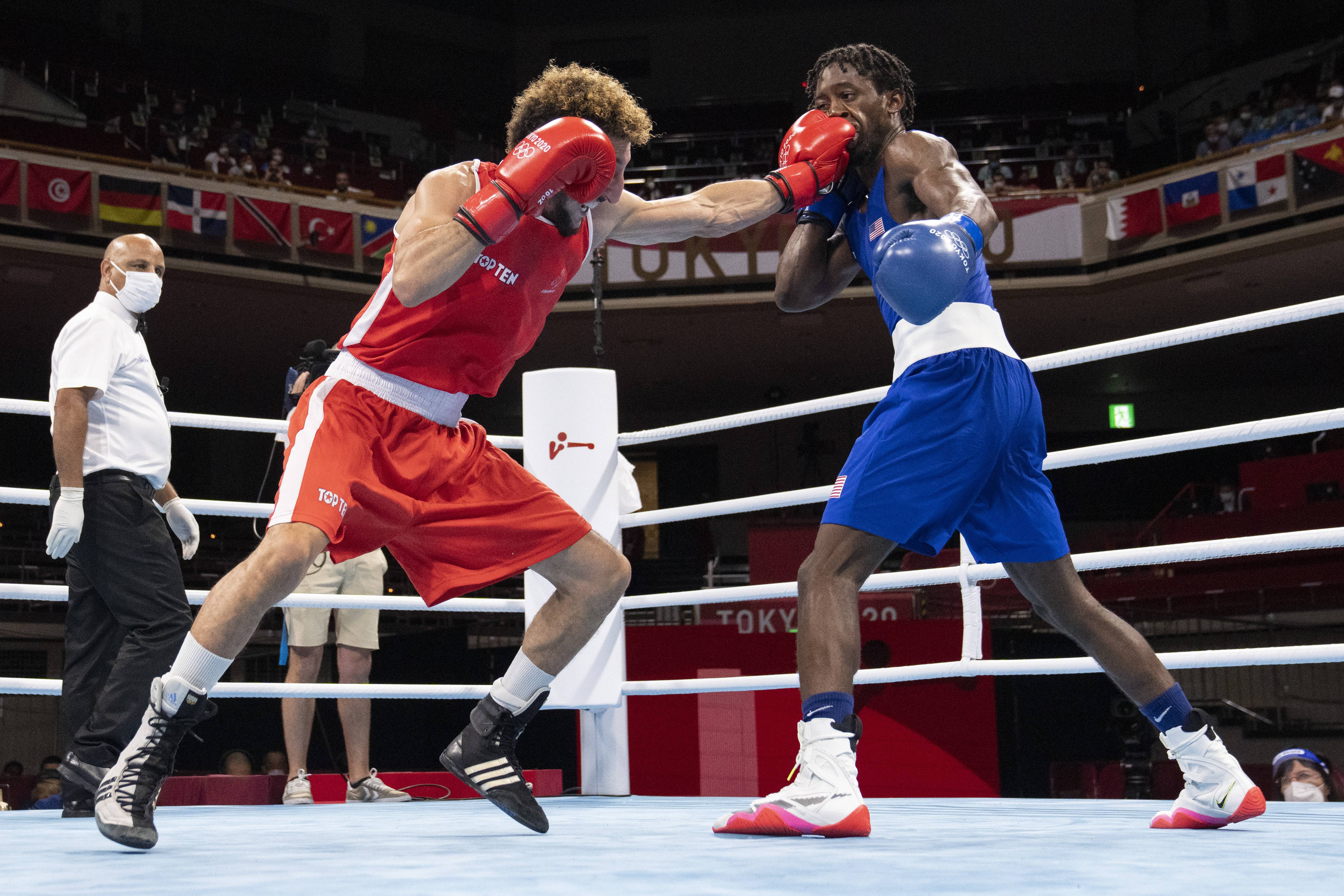 Jul 31, 2021; Tokyo, Japan; Keyshawn Davis (USA), blue gloves, and Sofiane Oumiha (FRA), red gloves, in the Men's Light (57-63kg) preliminaries during the Tokyo 2020 Olympic Summer Games at Kokugikan Arena. Davis won the bout over Oumiha after the referee stopped the contest. Mandatory Credit: Andrew P. Scott-USA TODAY Sports