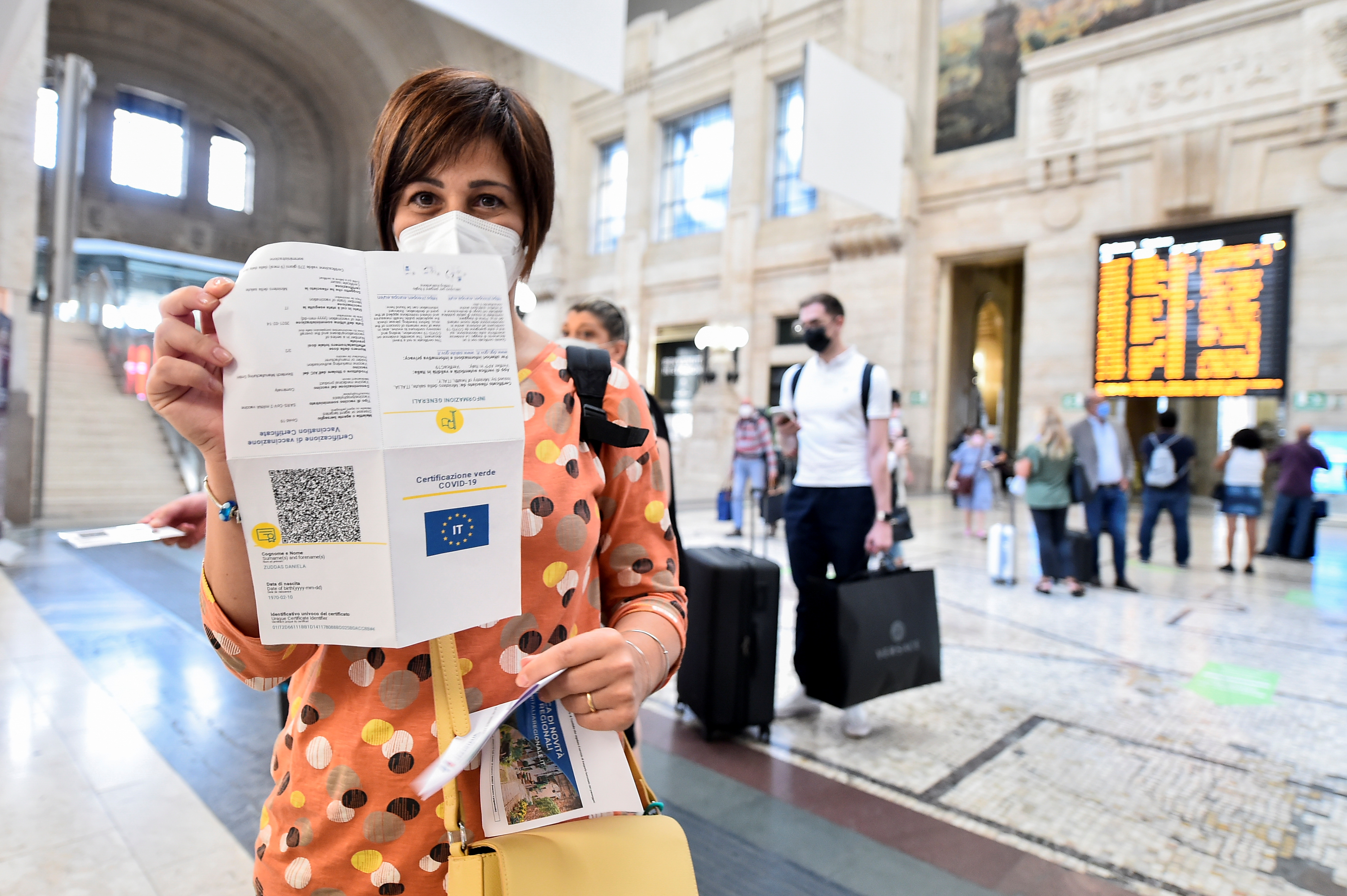 A woman shows her COVID-19 certificate at a train station in Milan, Italy, September 1, 2021. REUTERS/Flavio Lo Scalzo