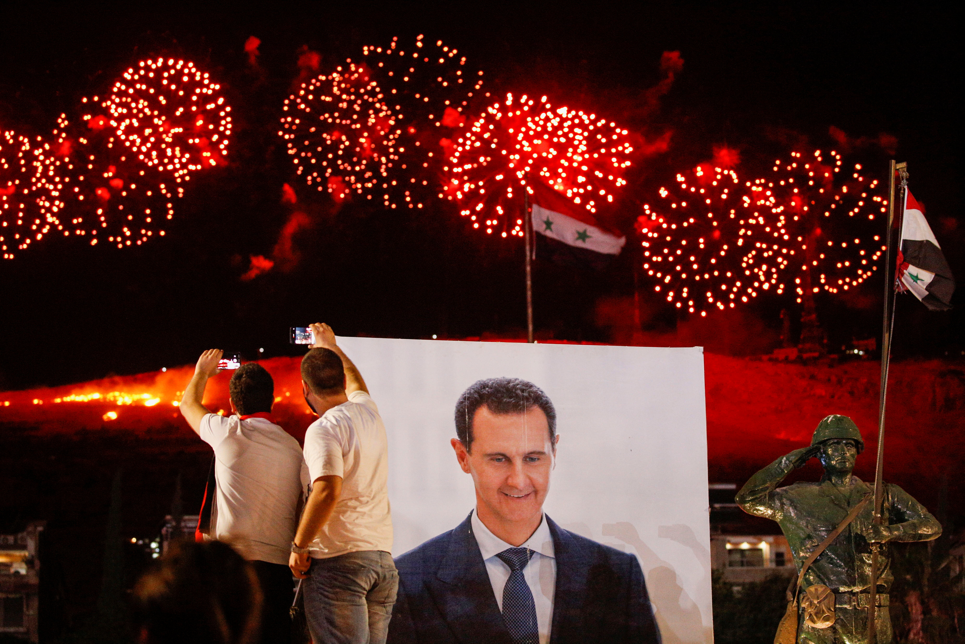 A poster depicting Syria's president Bashar al- Assad is seen as supporters of him celebrate after the results of the presidential election announced that he won a fourth term in office, in Damascus, Syria, May 27, 2021. REUTERS/Omar Sanadiki