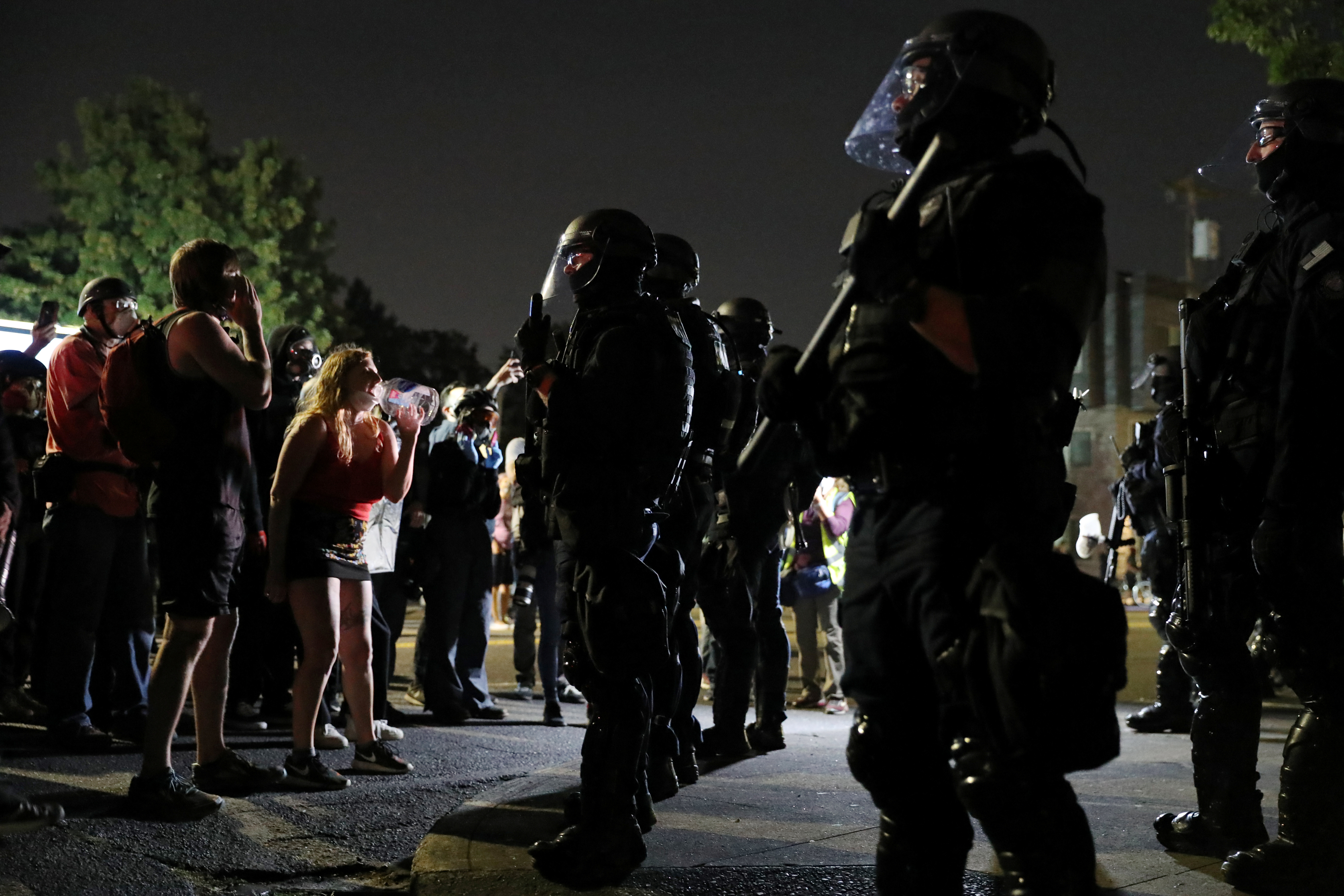 Protesters face off against Portland police officers as they demonstrate against police violence and systemic inequality for the 99th consecutive night in Portland, Oregon, U.S. September 4, 2020. REUTERS/Caitlin Ochs