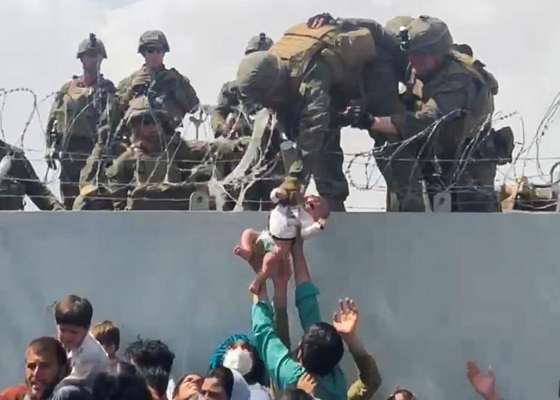 19 年 2021 月 19 日,阿富汗喀布尔,一名婴儿越过机场围墙被移交给美国军队,以便撤离,这张静态图像取自从社交媒体获得的视频。 视频拍摄于 2021 年 XNUMX 月 XNUMX 日。OMAR HAIDARI / via REUTERS