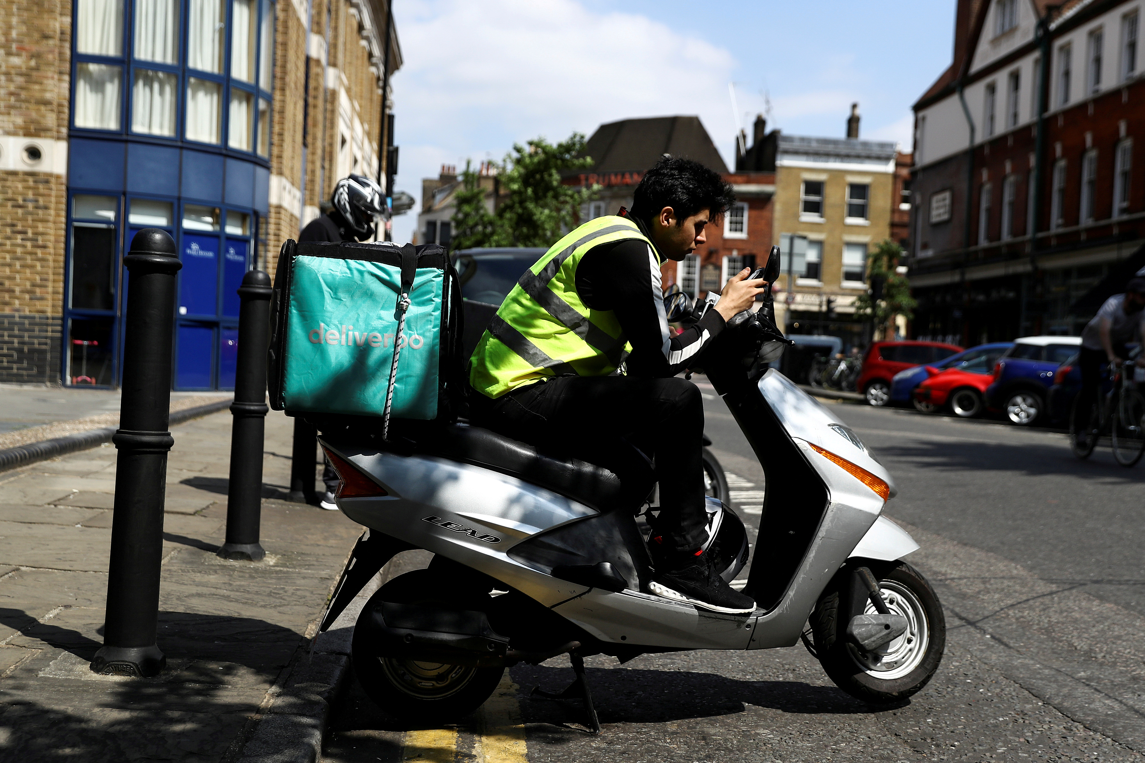 A Deliveroo scooter driver takes a break between deliveries in London, Britain June 8, 2018. REUTERS/Simon Dawson//File Photo