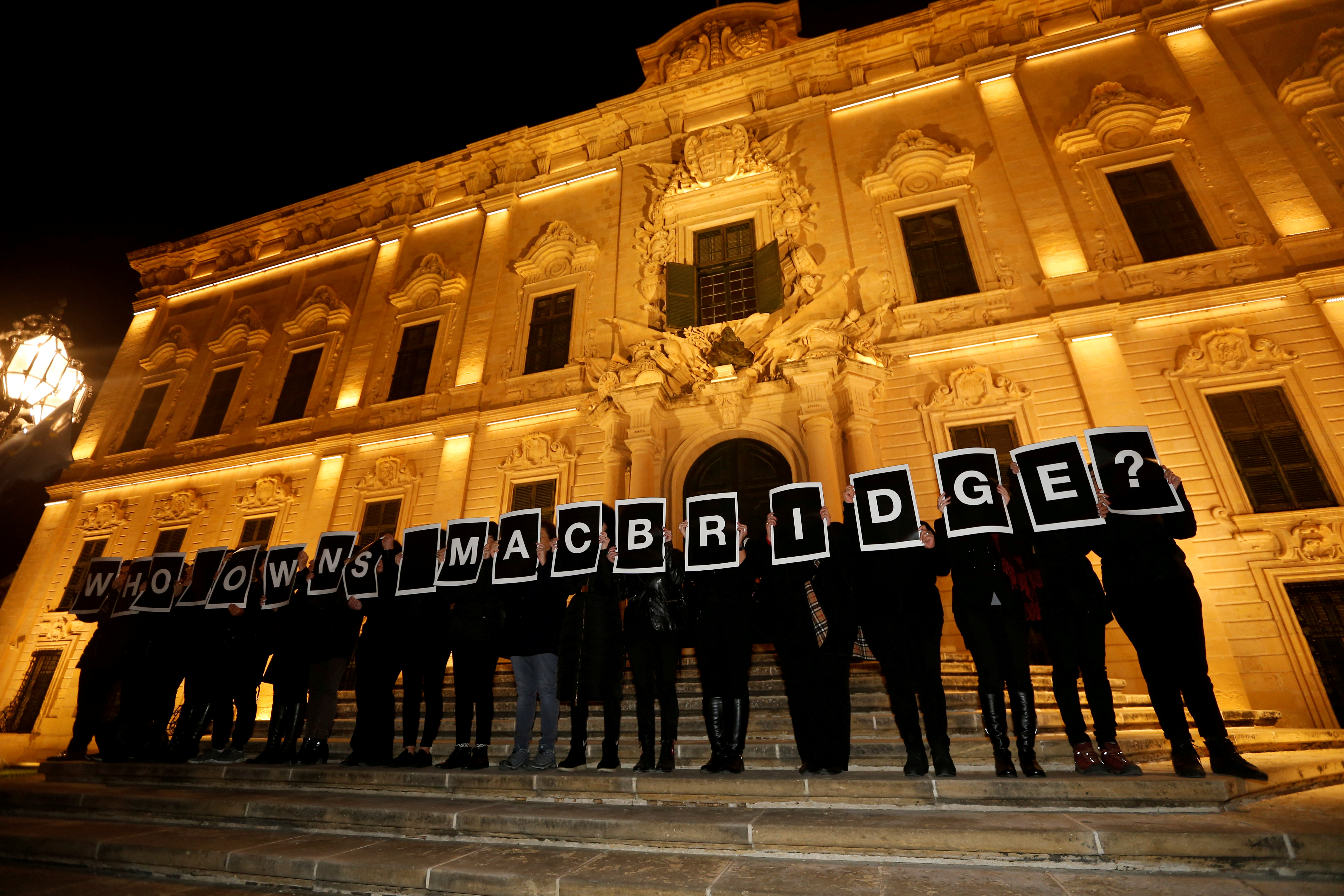 Activists from Occupy Justice Malta hold up placards reading