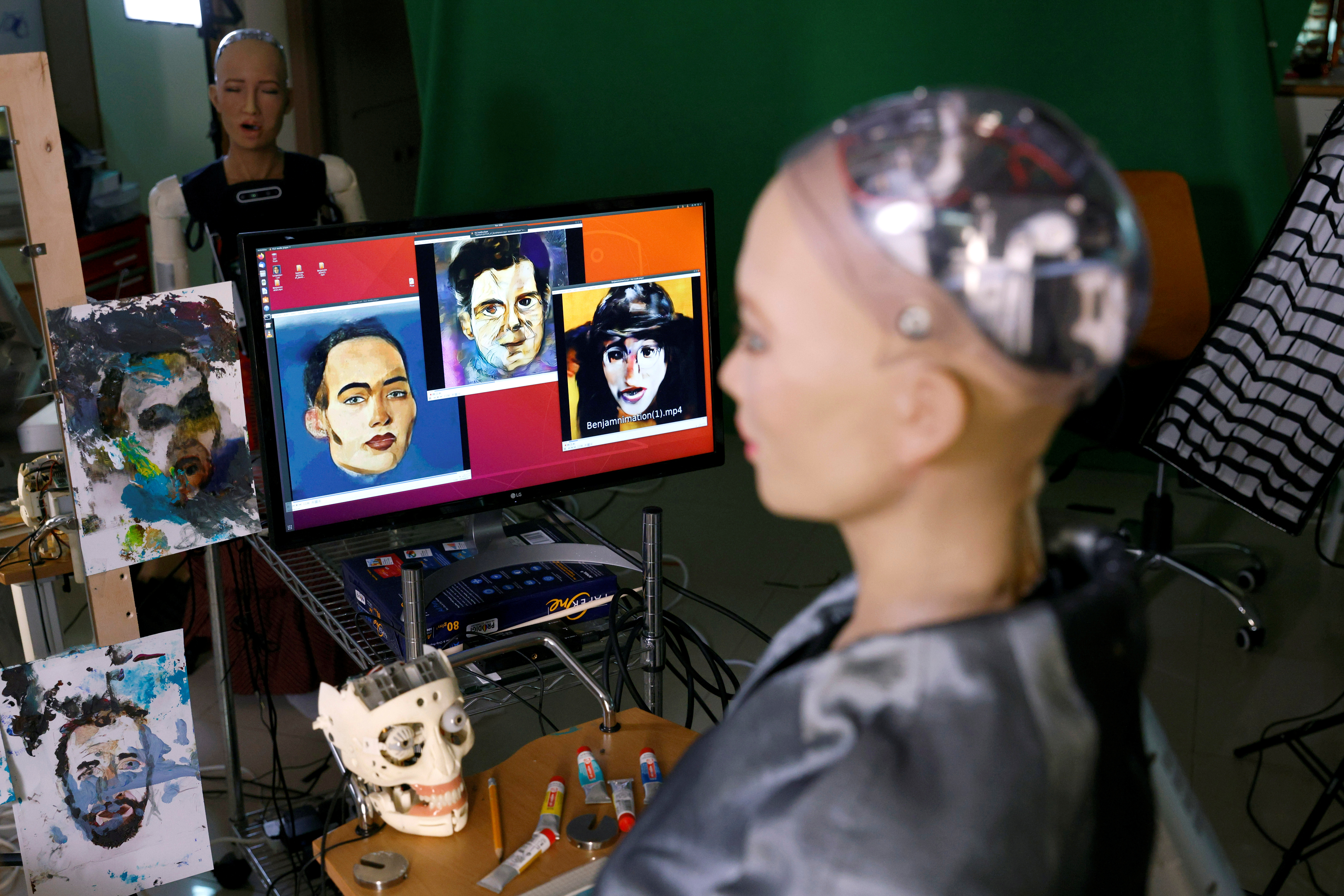 Sophia the humanoid robot, developed by Hanson Robotics, looks at paintings at her studio before auctioning her own non-fungible token (NFT) artwork, in Hong Kong, China March 16, 2021. REUTERS/Tyrone Siu