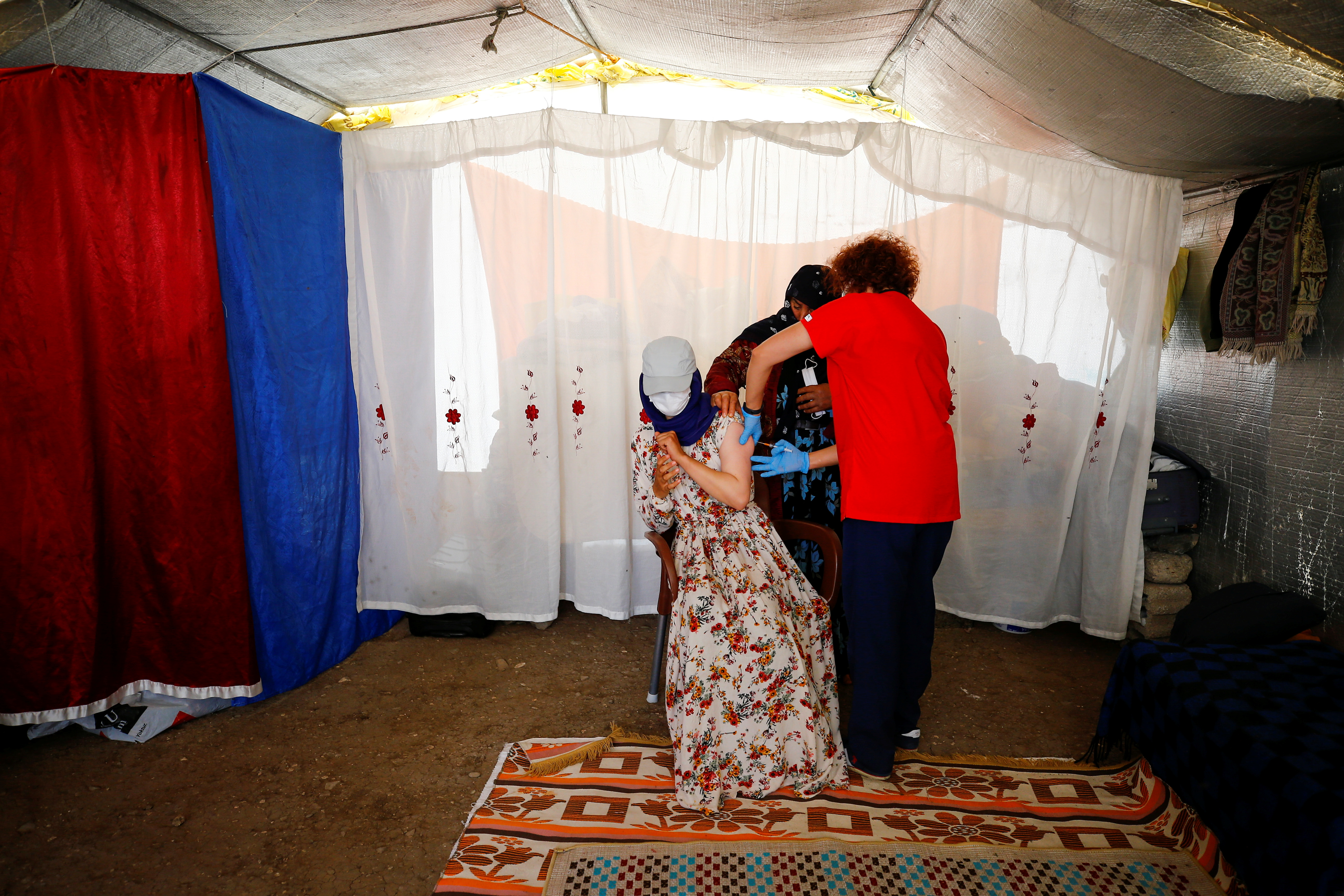 A seasonal farm worker receives a dose of the Pfizer-BioNTech coronavirus disease (COVID-19) vaccine in the village of Oguzlar near Polatli as nationwide vaccination continues, in Ankara, Turkey July 8, 2021. REUTERS/Cagla Gurdogan